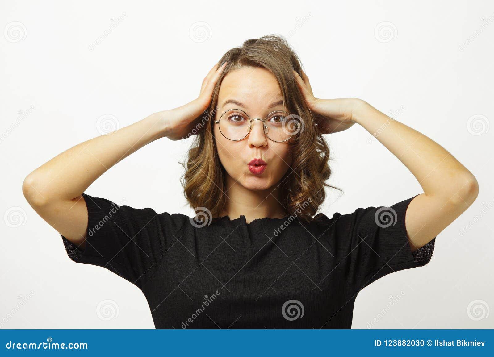 La mujer emocional en choque pone sus manos para dirigir, tira de los labios con el tubo, los ojos abiertos de par en par, sorpre