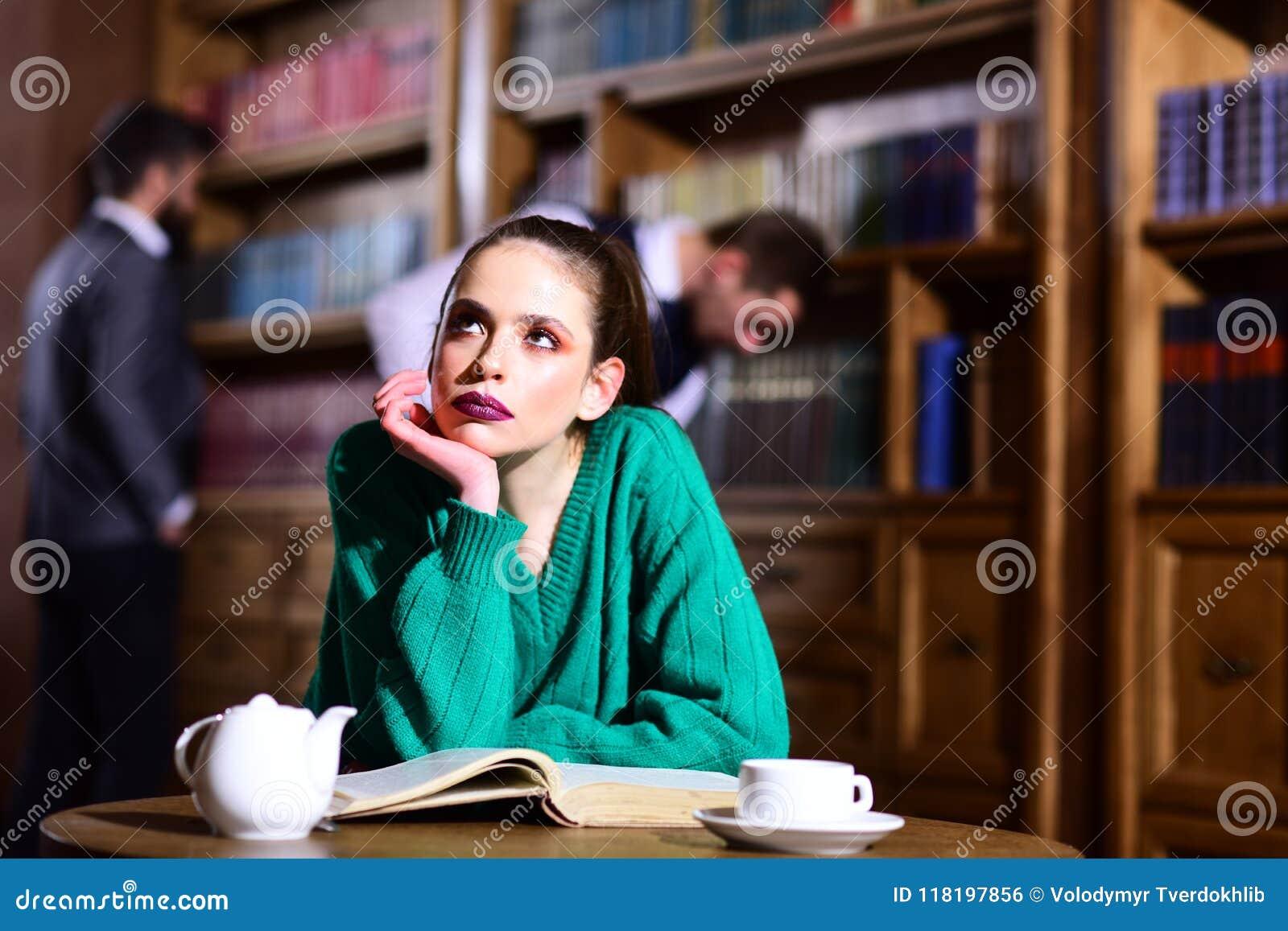 La mujer en biblioteca leyó el libro en el café de consumición de la tetera de la taza café de la literatura con la muchacha y lo