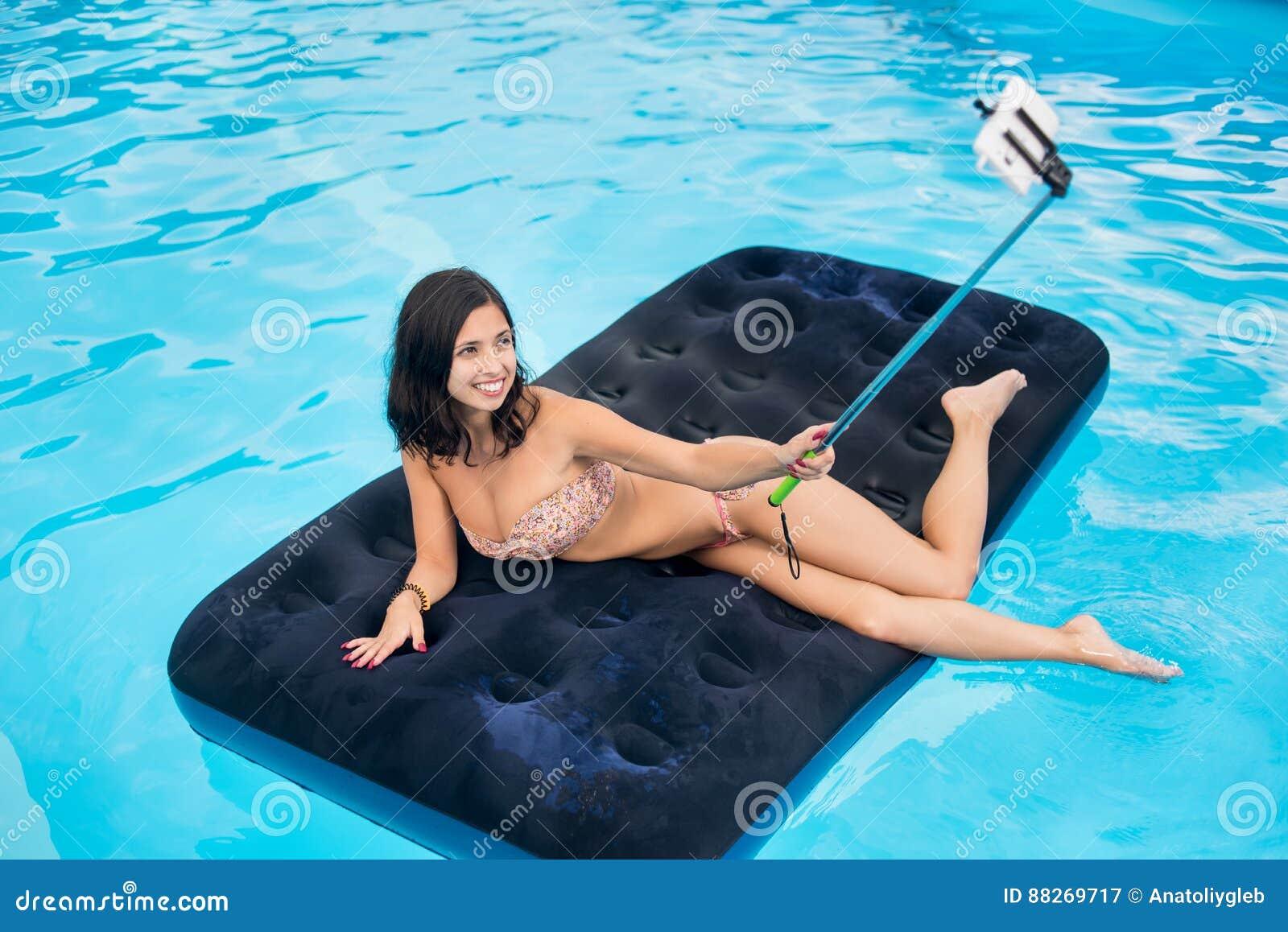 La mujer en bikini que sonríe y hace la foto del selfie en el teléfono con el palillo del selfie en un colchón en la piscina en e