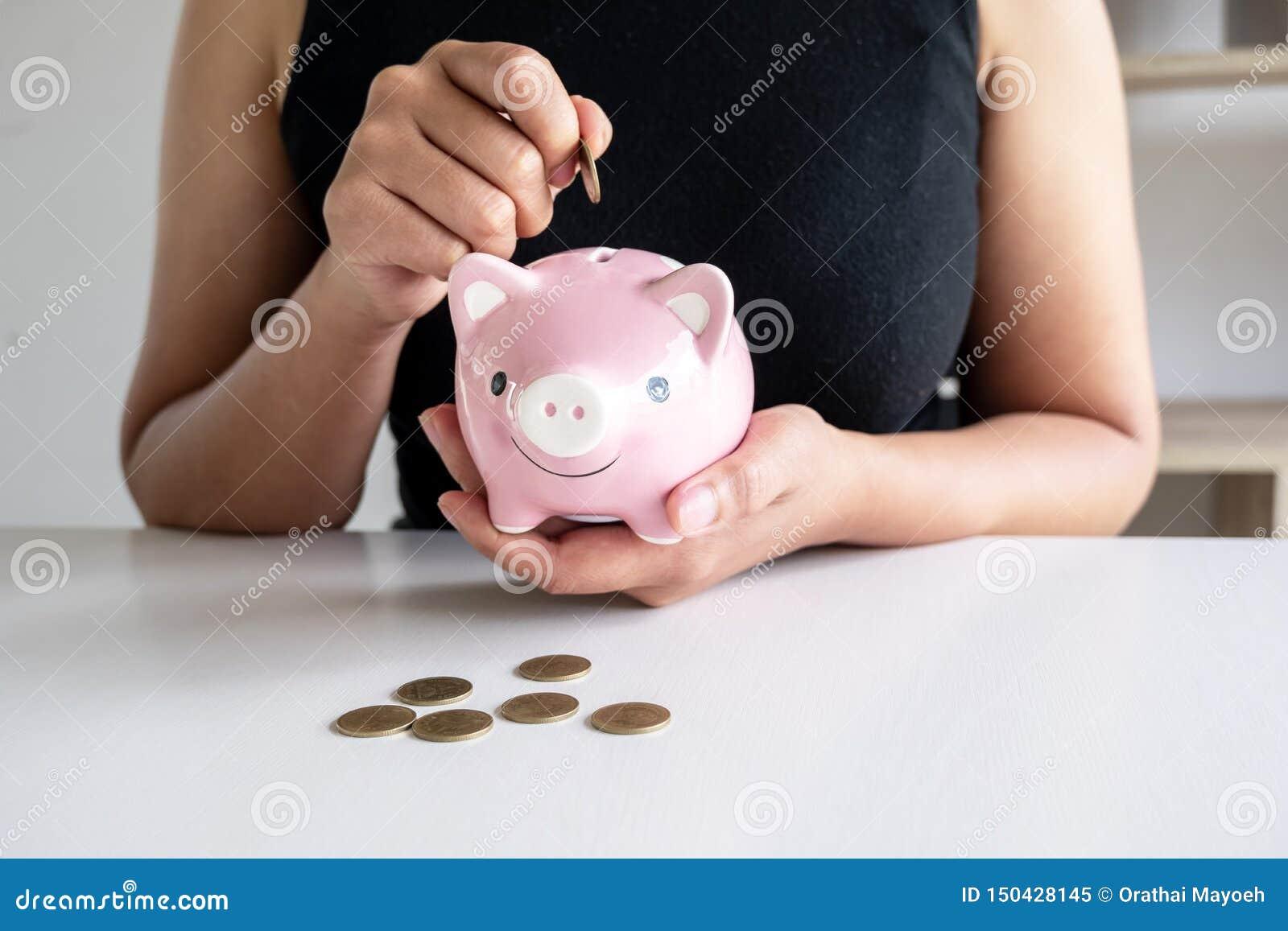 La mujer en camisa negra enseña a equipos a poner la moneda en la hucha rosada