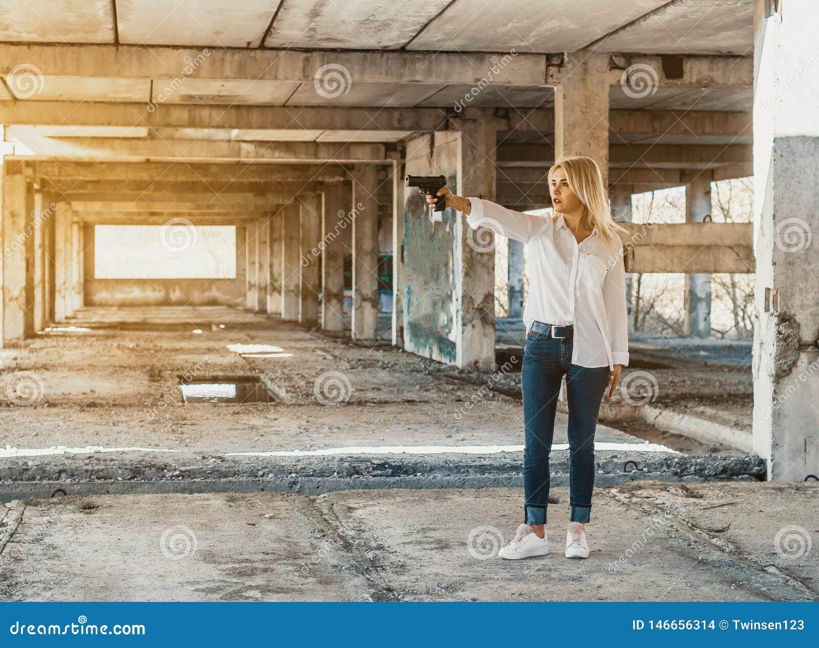 La mujer en los soportes blancos de la camisa en un edificio abandonado, tira un arma
