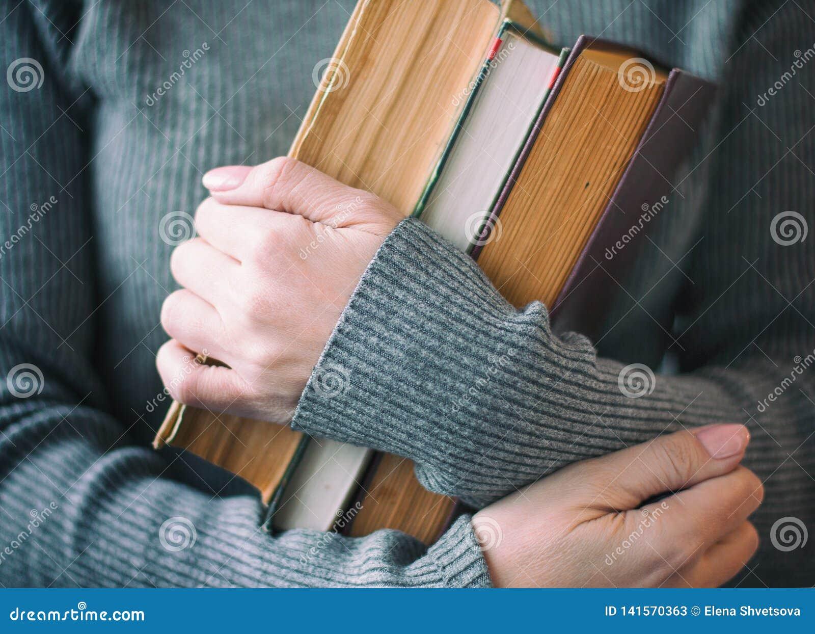 La mujer en ropa gris sostiene tres libros a disposición