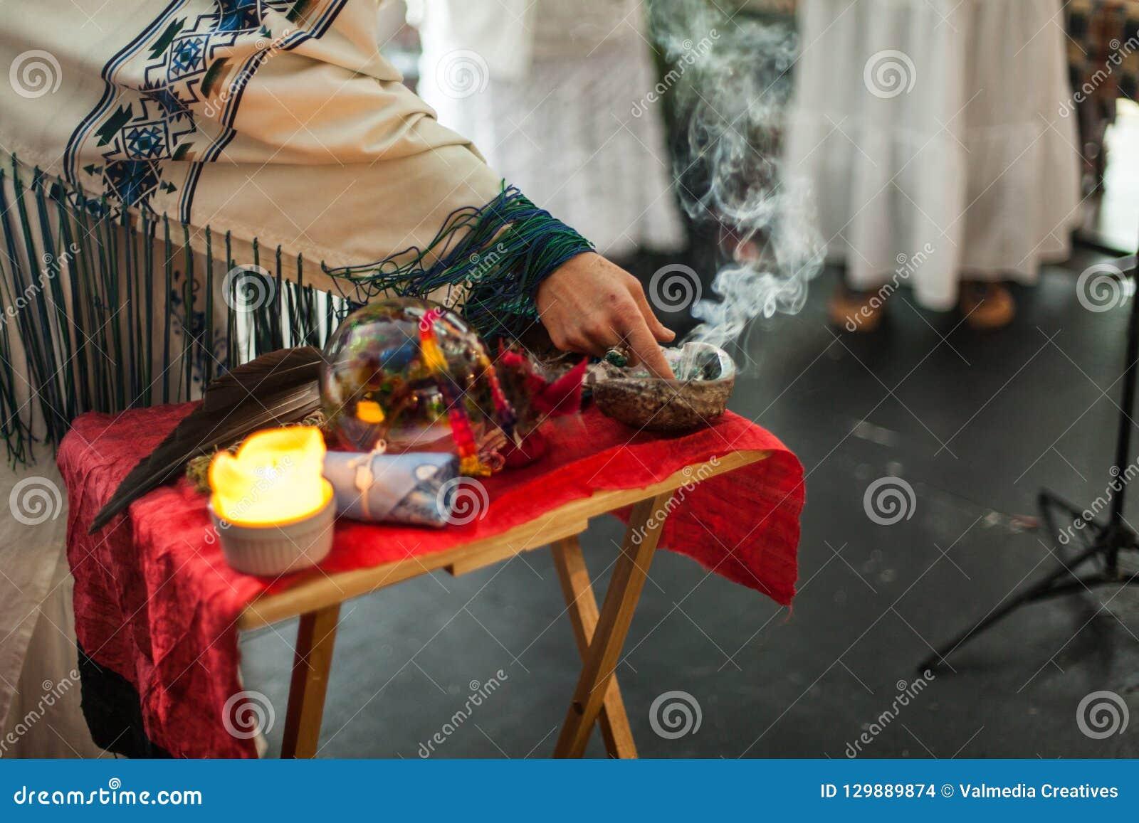 La mujer en traje ceremonial está tocando el sabio que fuma