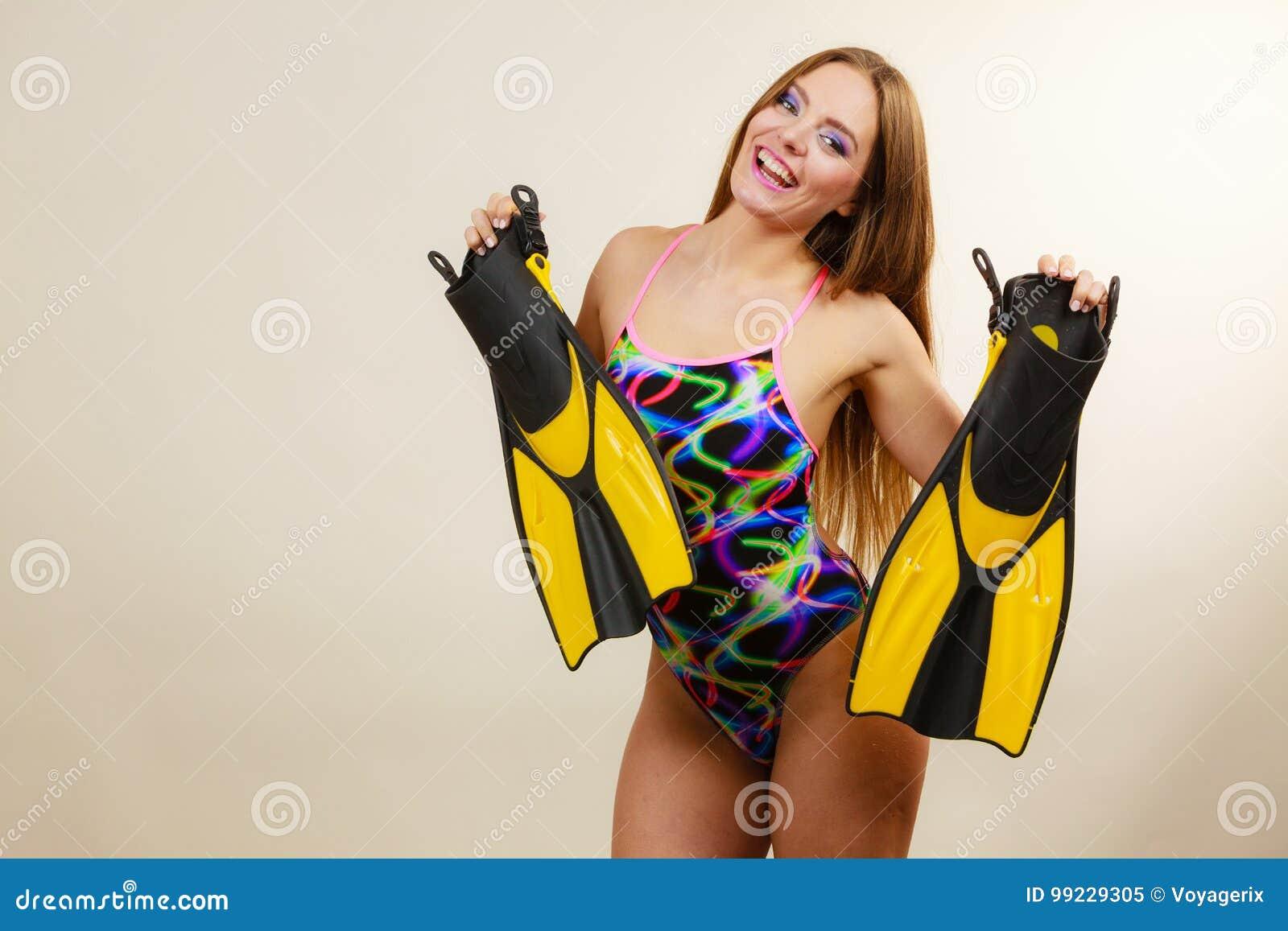 77218c953 La Mujer En Traje De Baño Sostiene Las Aletas Que Se Divierten ...