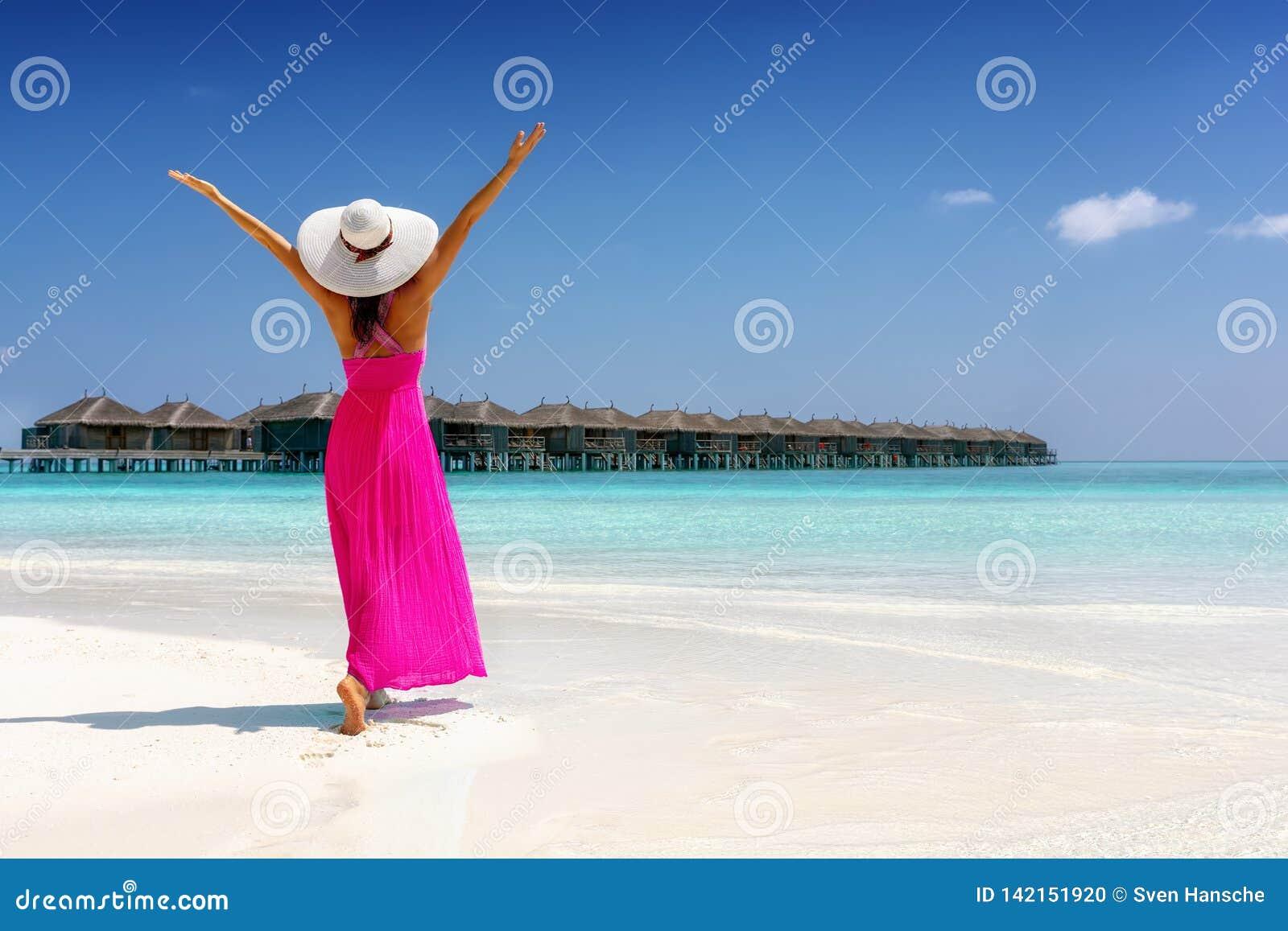 La mujer en un vestido rosado del verano se coloca en una playa tropical en los Maldivas