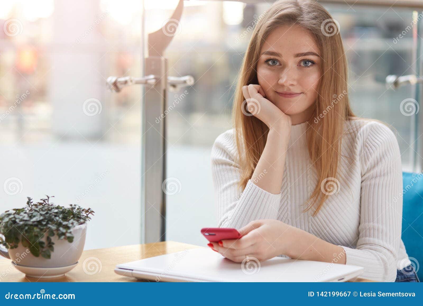 La mujer encantadora con sonrisa hermosa sostiene el teléfono móvil a disposición, guarda otra mano en la barbilla, tiene resto e