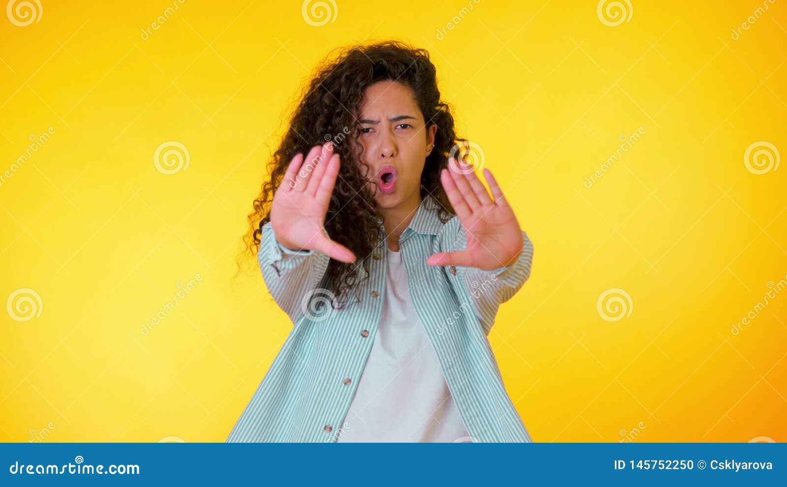 La mujer enfadada enojada que aumenta la mano hasta dice no la parada Mirada esc?ptica y desconfiada, sintiendo enojada en alguie