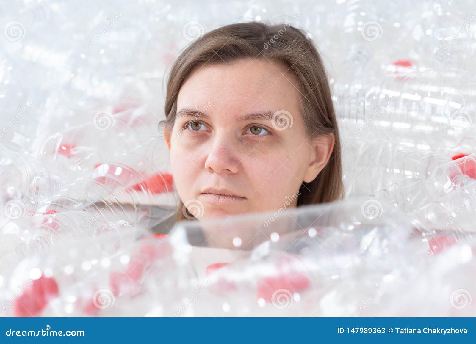 La mujer enferma deshidratada est? mintiendo en una pila de botellas pl?sticas Problema de la contaminaci?n ambiental Basura de l
