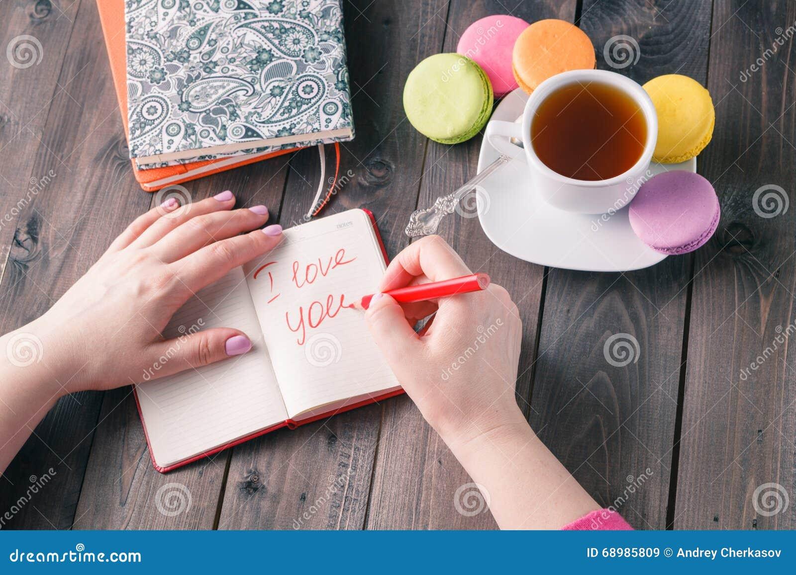La mujer escribe la letra te quiero mientras que bebe el café