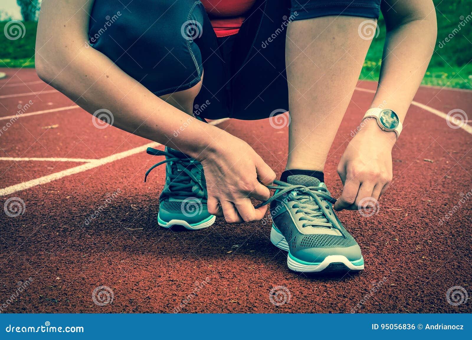 Corriente Estadio Zapatos En Pista Sus La Atando Está Una Mujer Del qCwWBZ8
