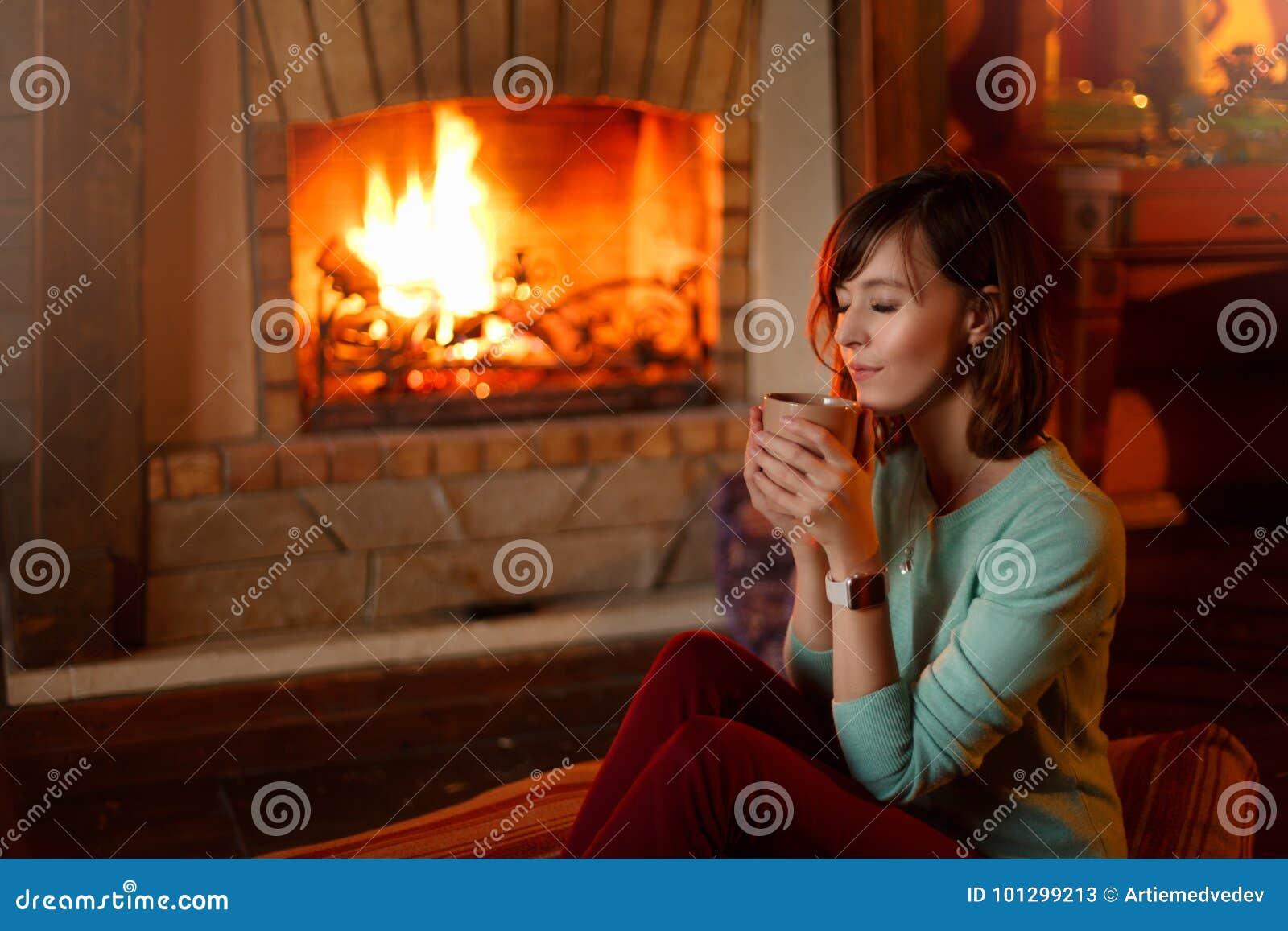 La mujer está bebiendo té y se está calentando por la chimenea La hembra caucásica joven sostiene la taza de café en casa calient