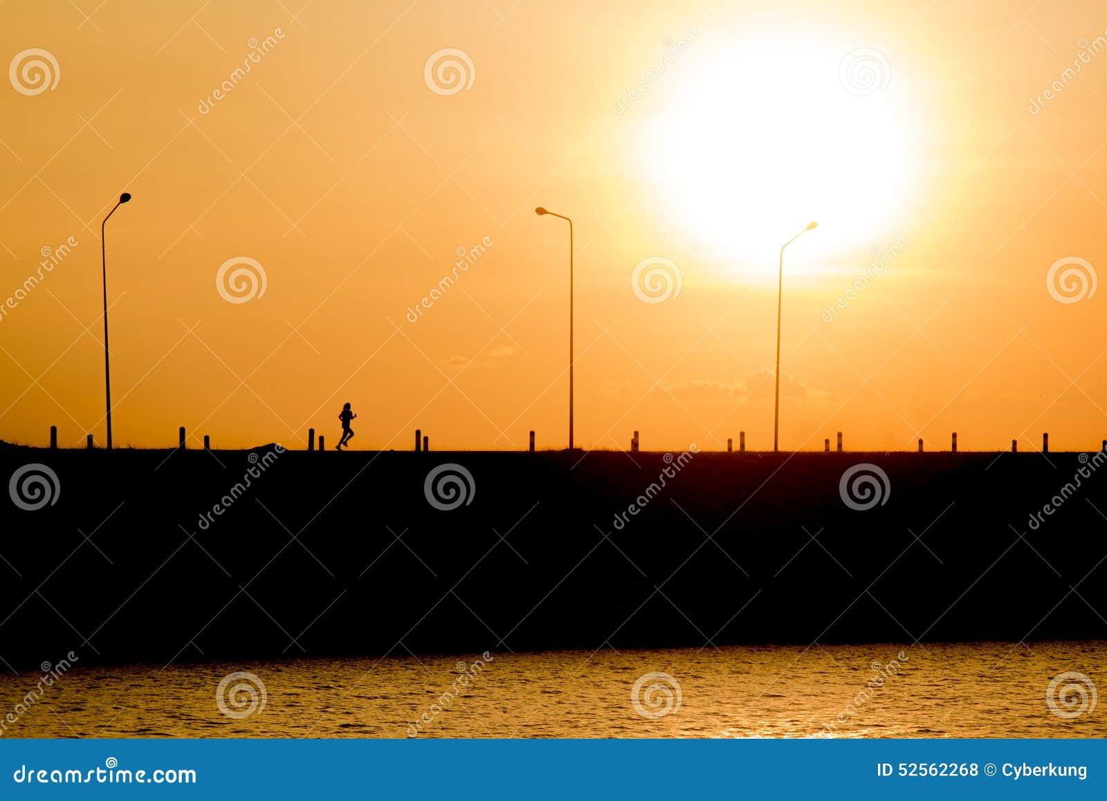La mujer está corriendo en la puesta del sol (la silueta)