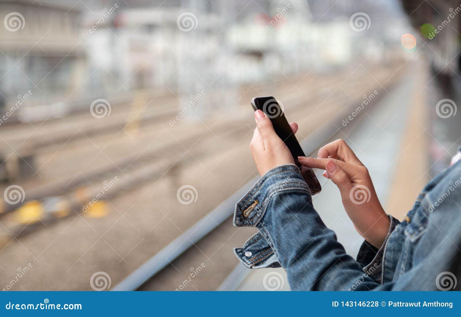 La mujer está leyendo el mensaje de texto en el teléfono móvil