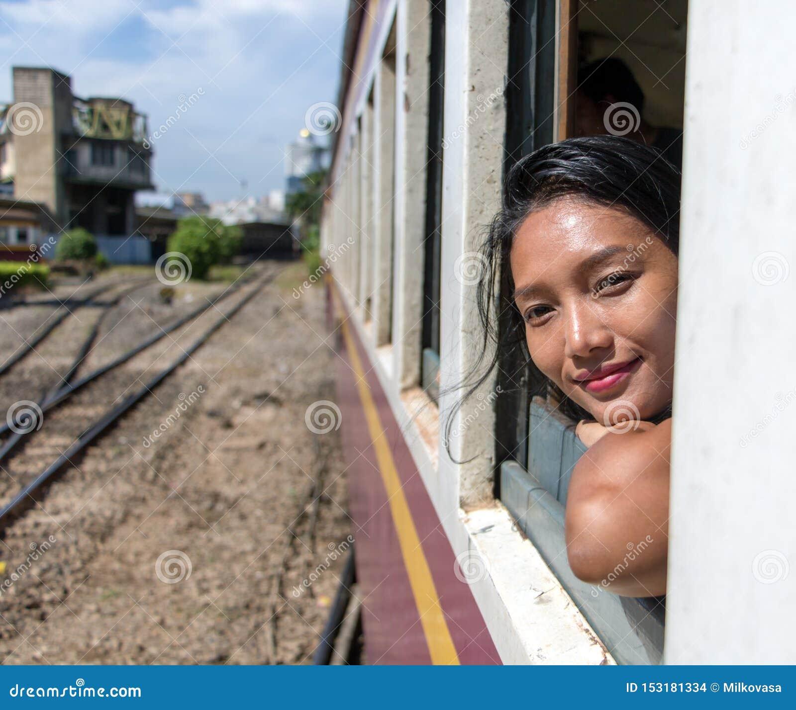 La mujer está mirando fuera de la ventana de un tren móvil