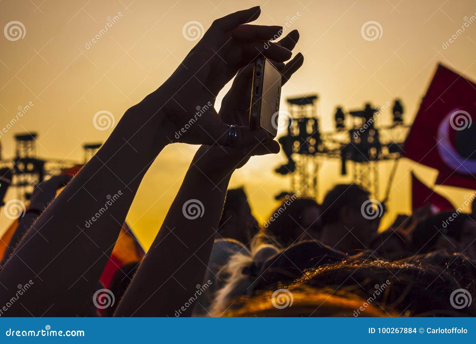 La mujer está tirando el vídeo con su smartphone en la puesta del sol