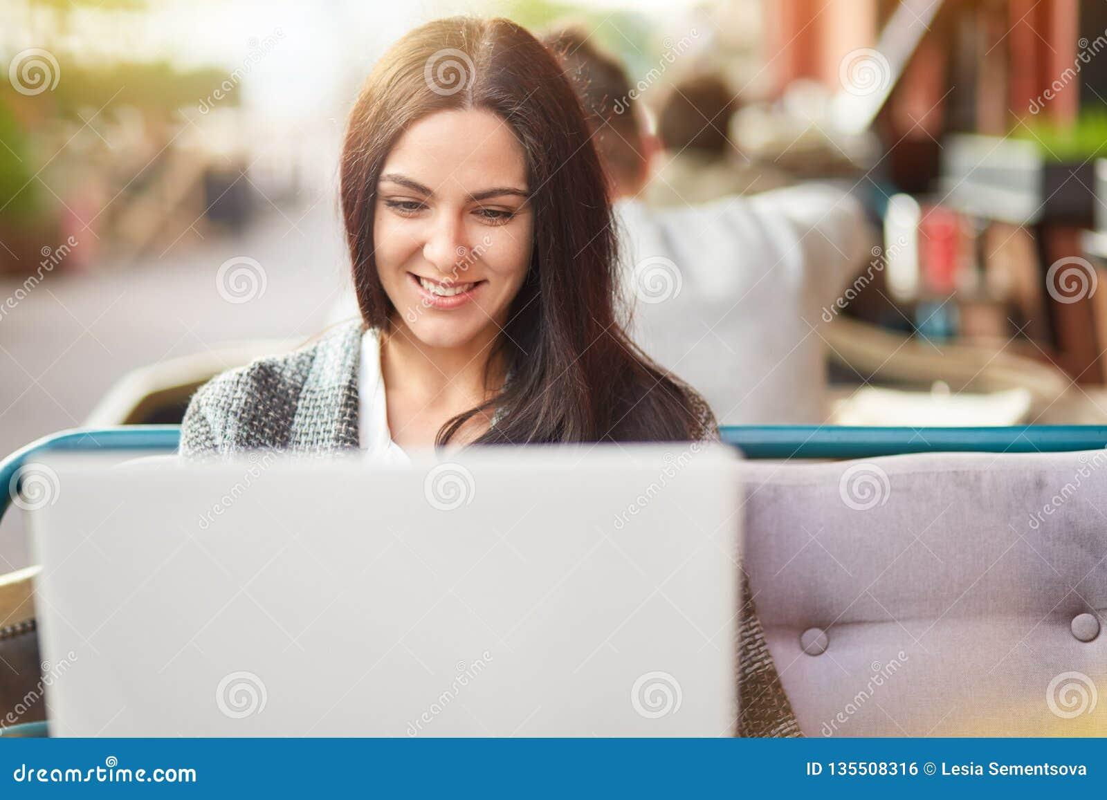 La mujer europea positiva tiene sonrisa dentuda, trabajos en el netbook digital, se sienta en el sofá cómodo en café del aire abi
