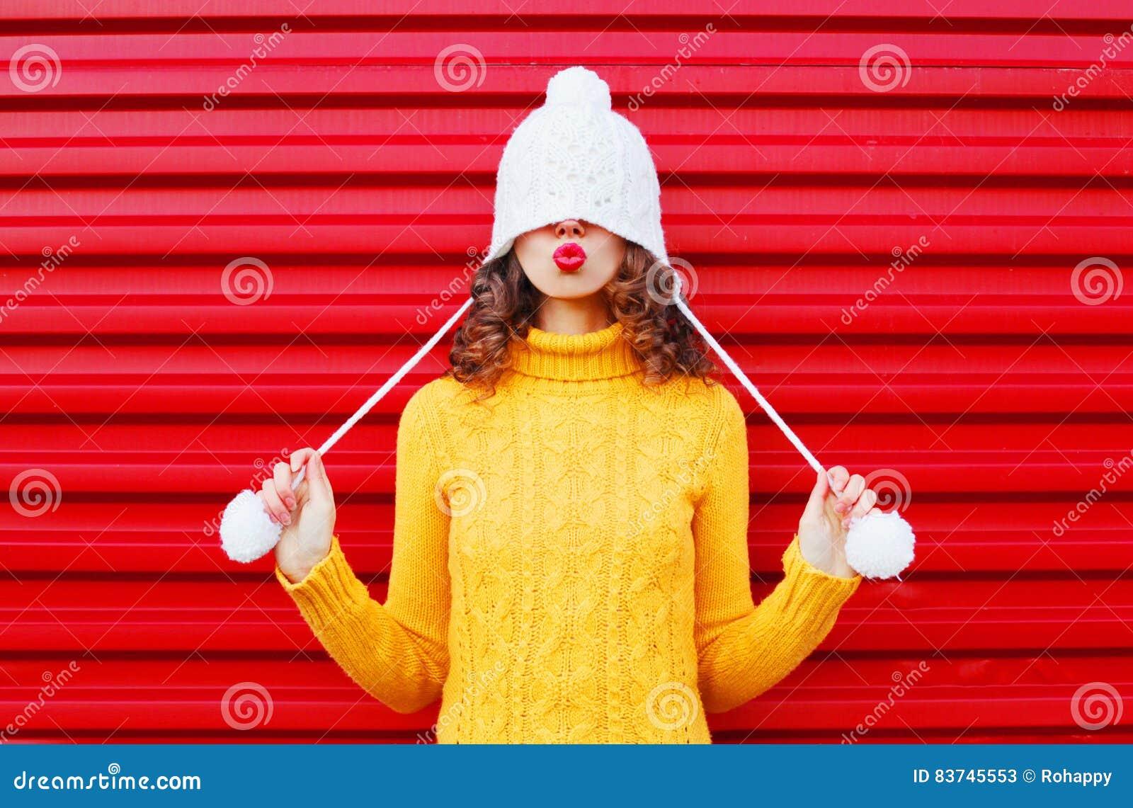 La mujer feliz de la moda que sopla los labios rojos hace que el aire besa el sombrero hecho punto colorido que lleva, suéter ama