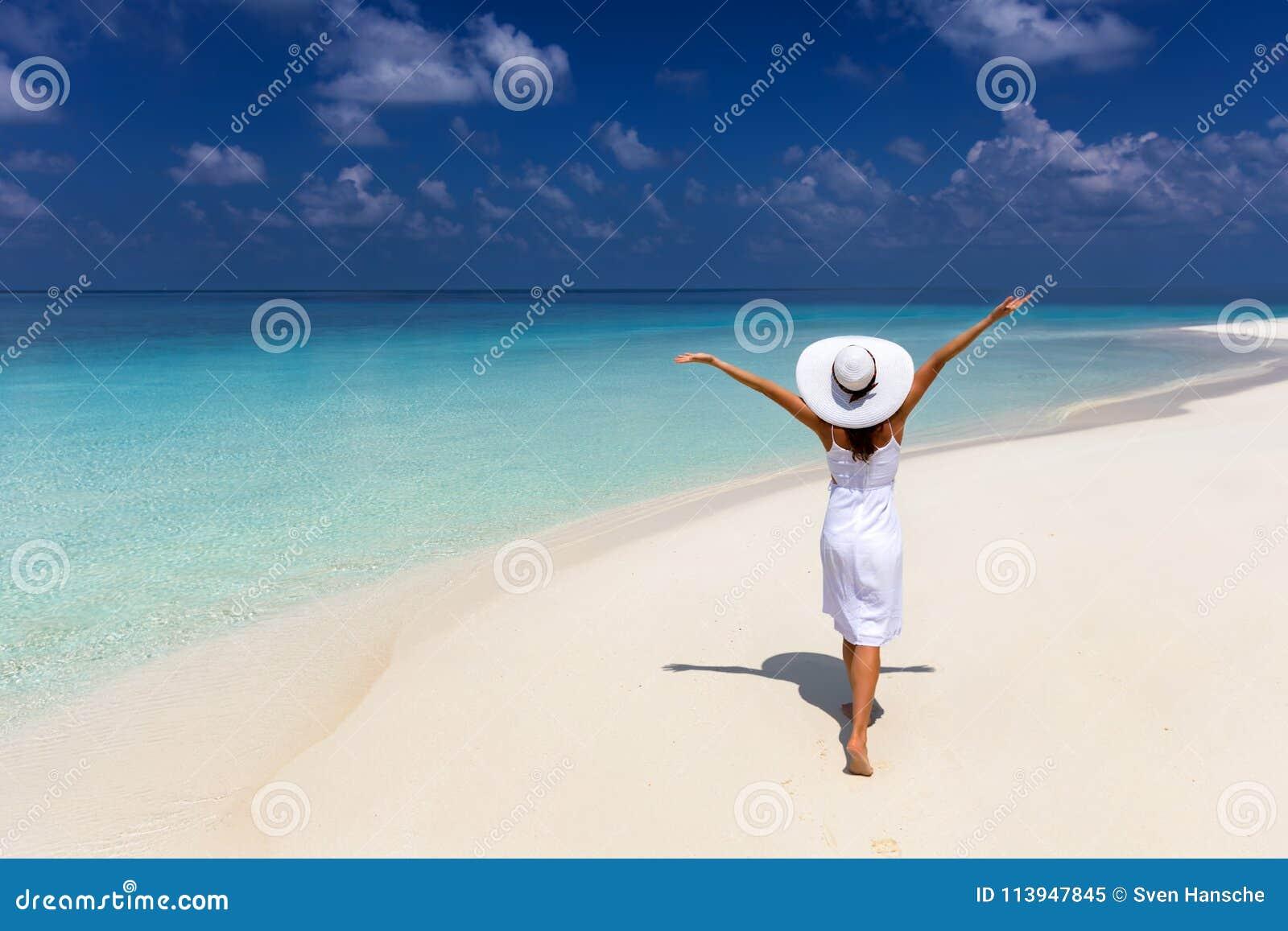 La mujer feliz del viajero disfruta de sus vacaciones de verano en una playa tropical