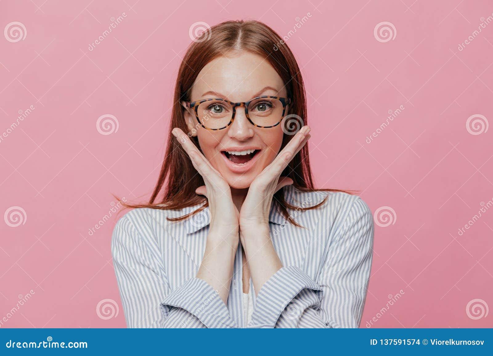 La mujer feliz guarda las manos debajo de la barbilla, siente encantada y satisfecha, lleva los vidrios ópticos y la camisa forma