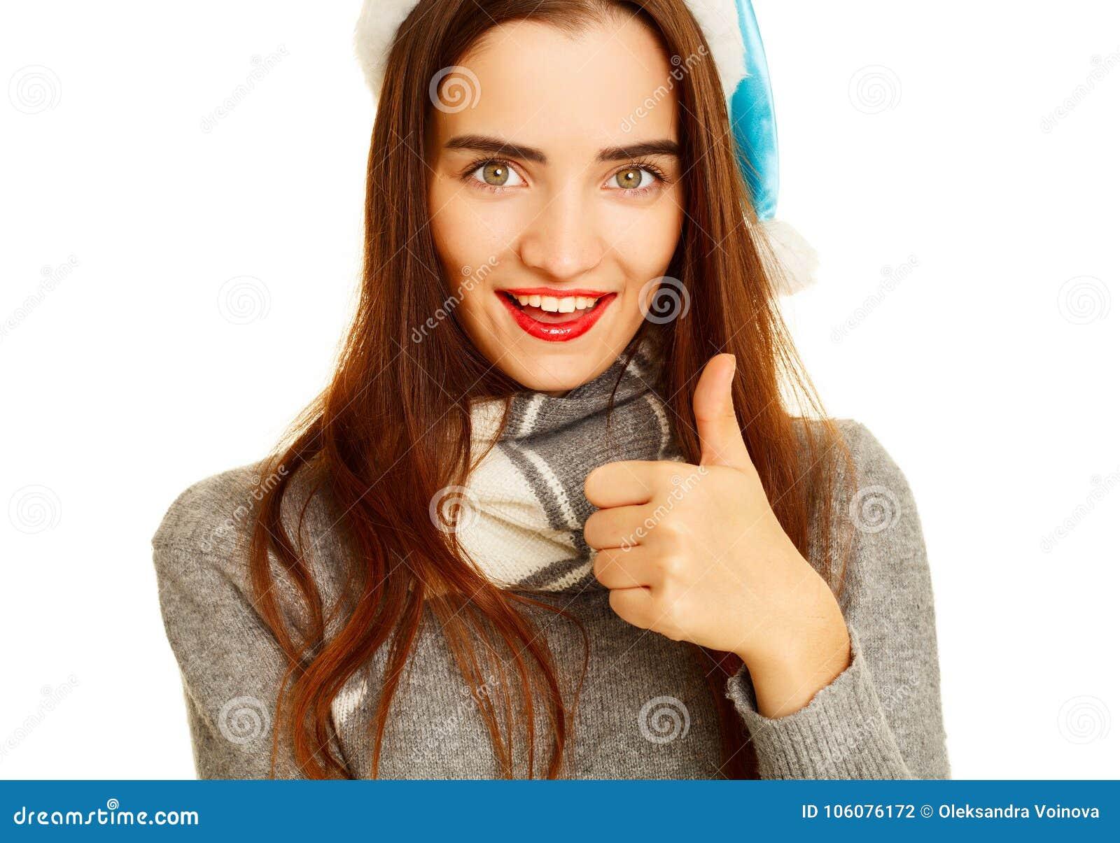 La mujer feliz joven en el sweather caliente que muestra la autorización de la mano firma encima el wh