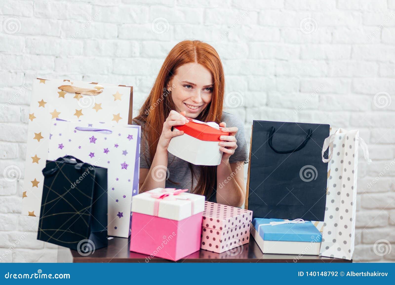 La mujer feliz joven tiene los regalos de parientes en su cumpleaños