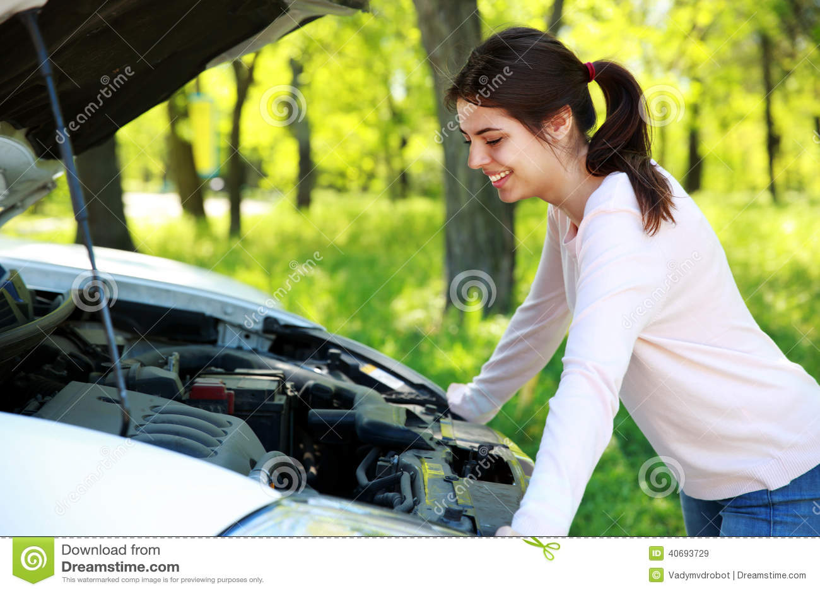 La mujer feliz mira debajo del coche de la capilla