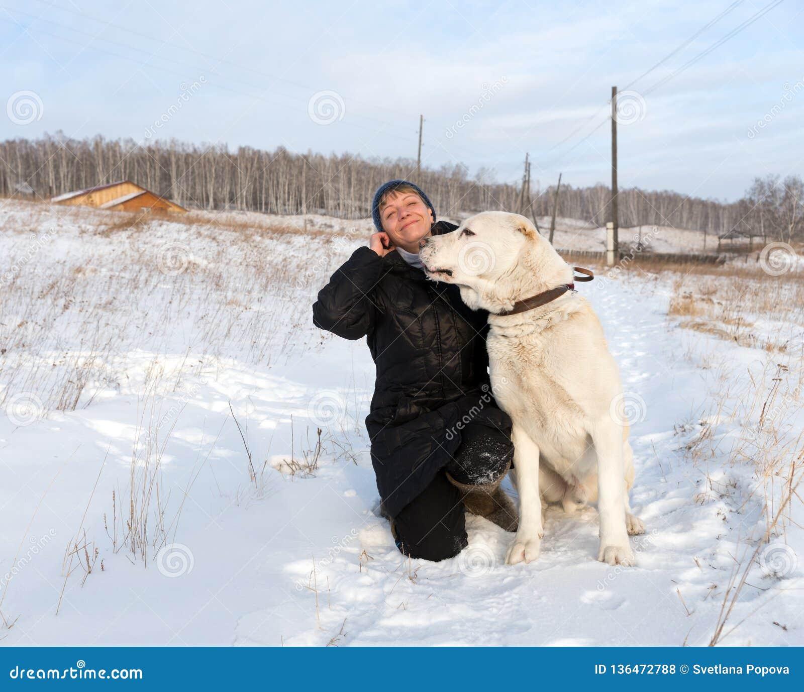 La mujer feliz se está sentando con un pastor asiático central en un camino rural del invierno contra el contexto del pueblo