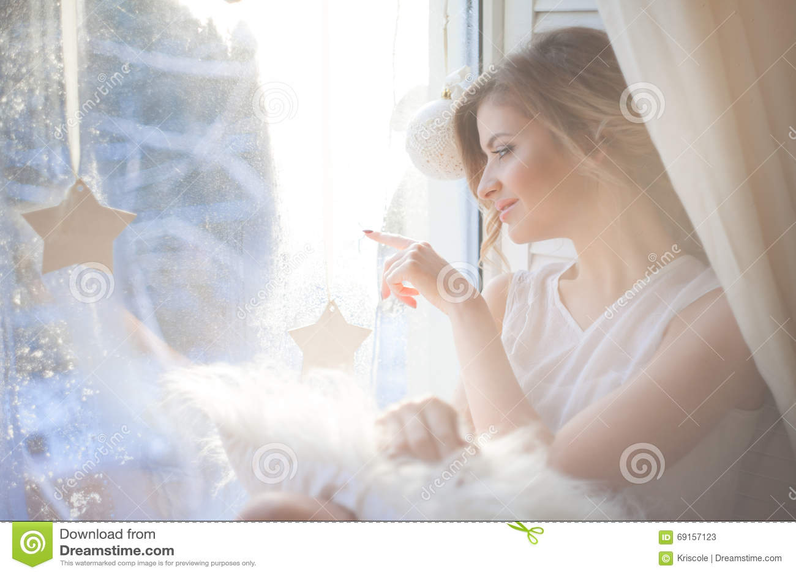 La mujer hermosa con maquillaje diario fresco y el peinado ondulado romántico, sentándose en el alféizar, dibuja sobre el vidrio