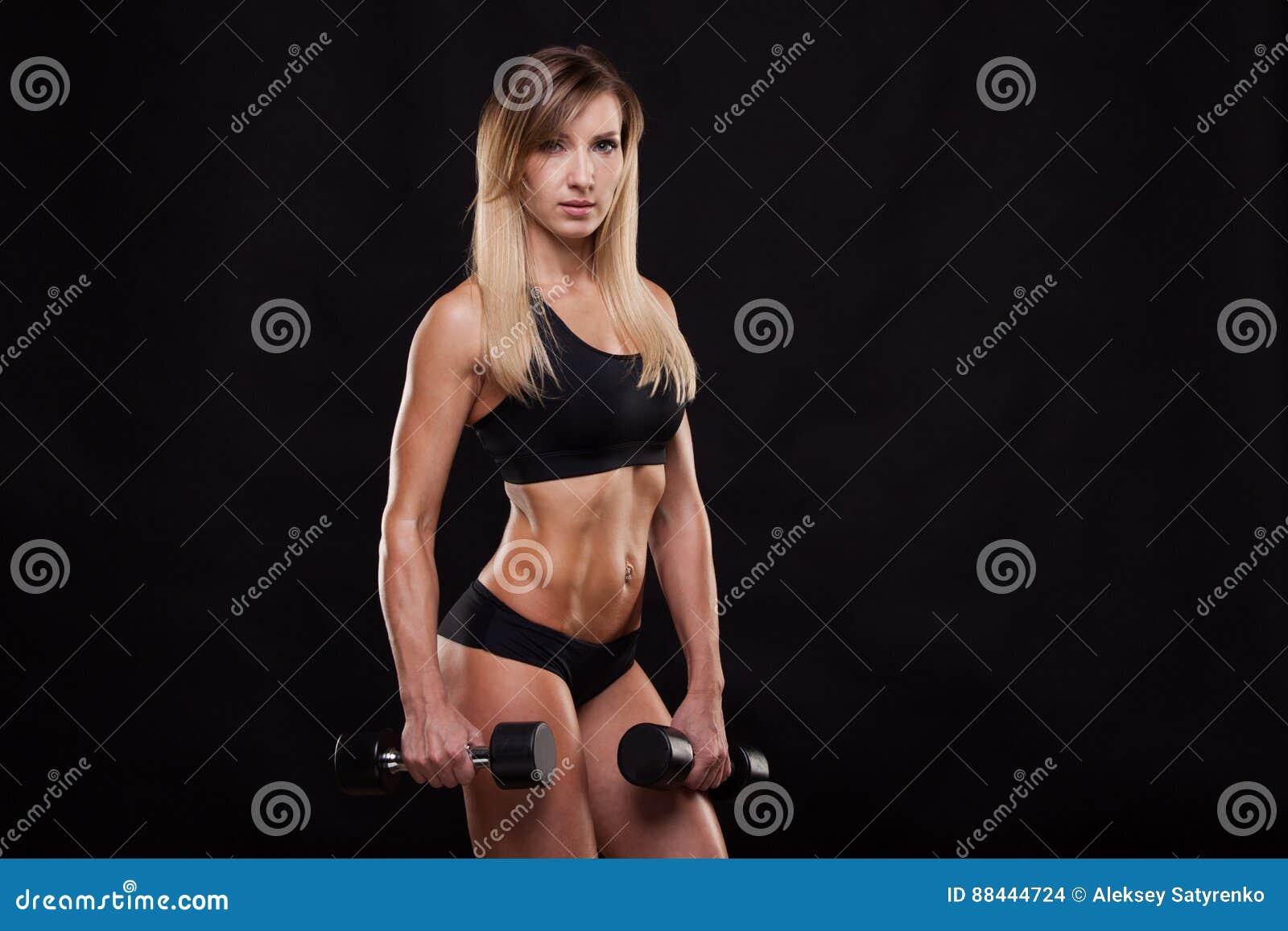 La mujer hermosa de la aptitud está levantando pesas de gimnasia Muchacha deportiva que muestra su cuerpo bien entrenado Aislado