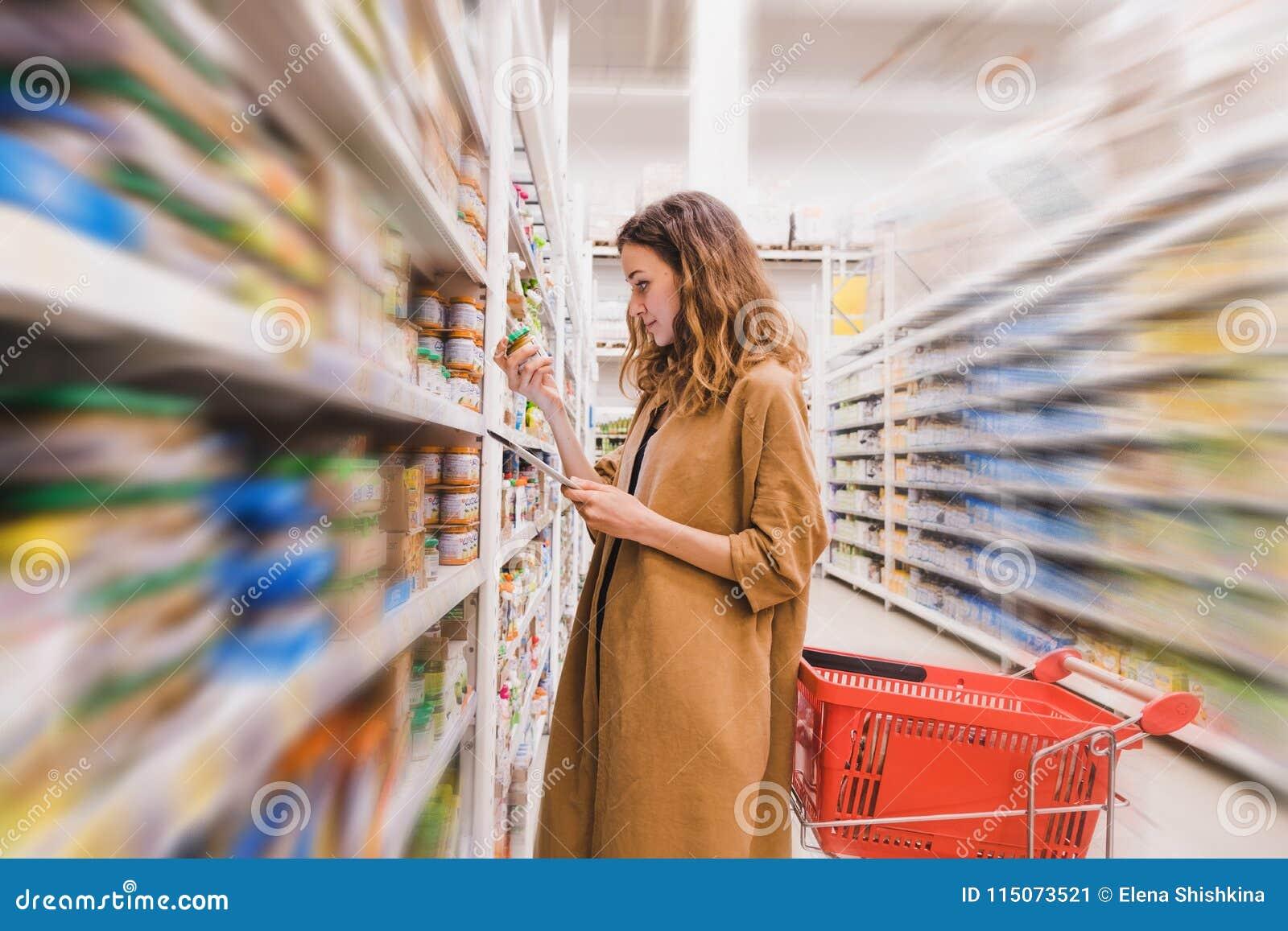 La mujer hermosa joven con una tableta escoge los alimentos para niños en un supermercado, fondo borroso