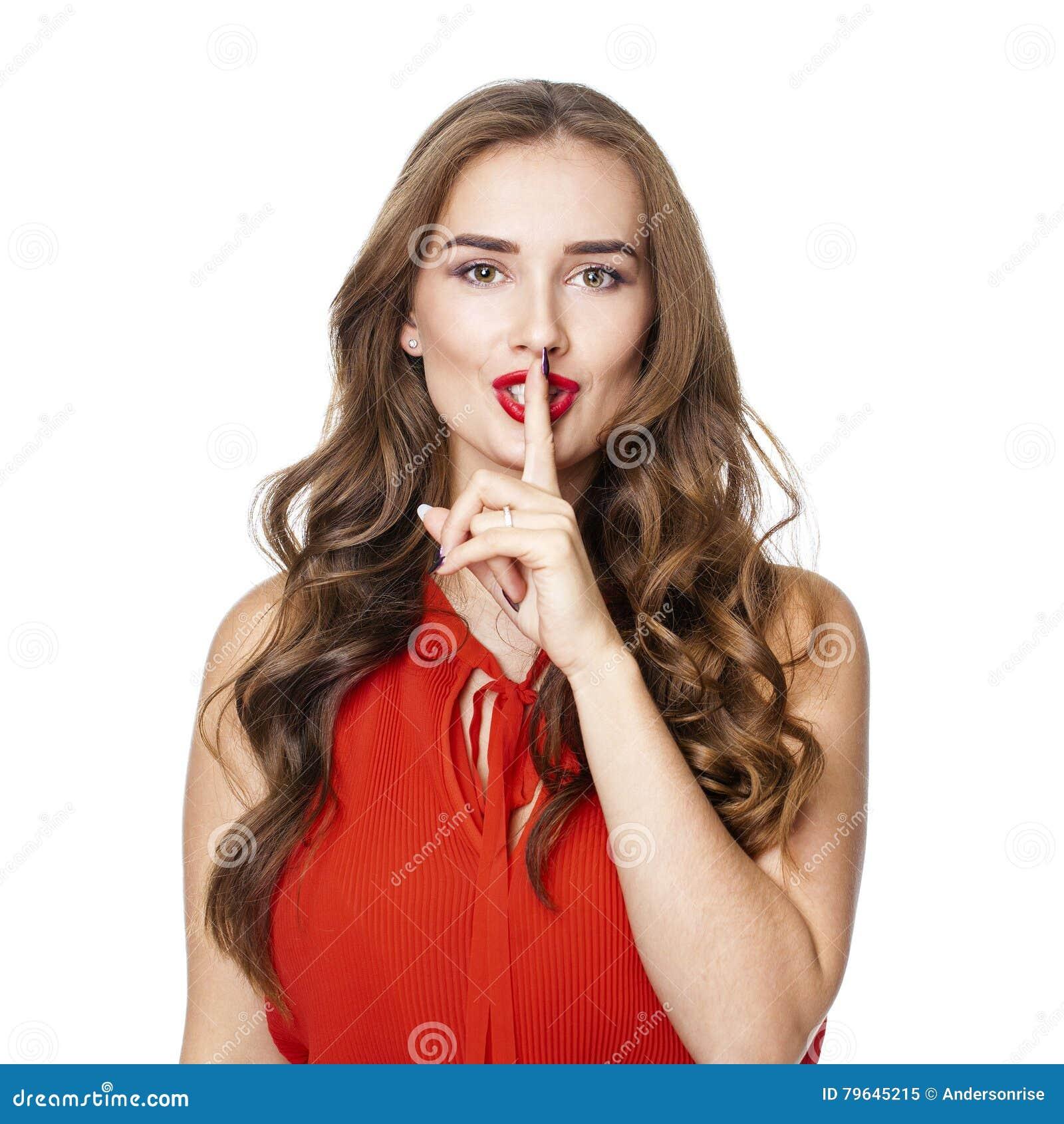 La mujer hermosa joven ha puesto el índice a los labios como muestra de sile