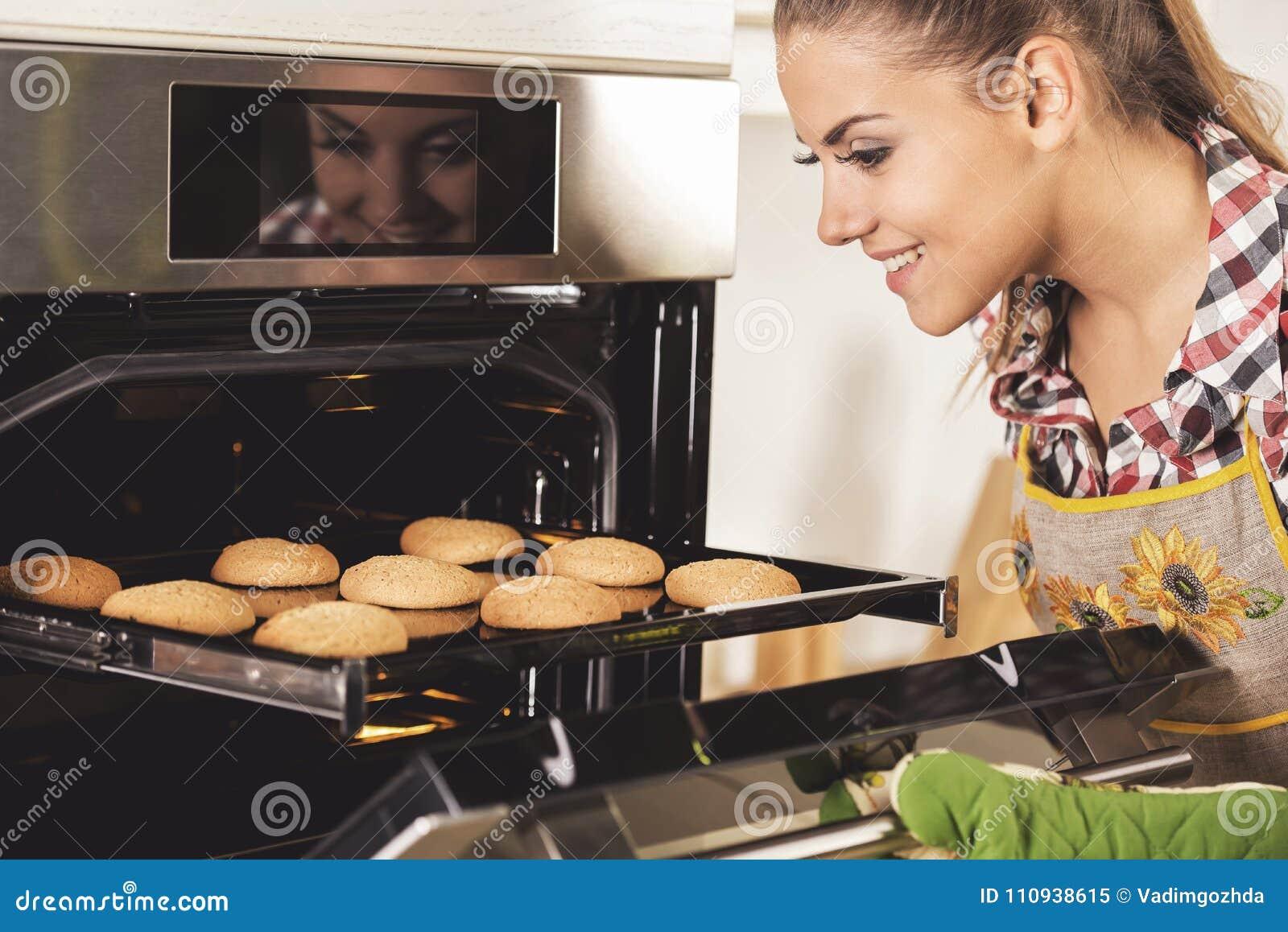 La mujer hermosa joven tira de las galletas del horno