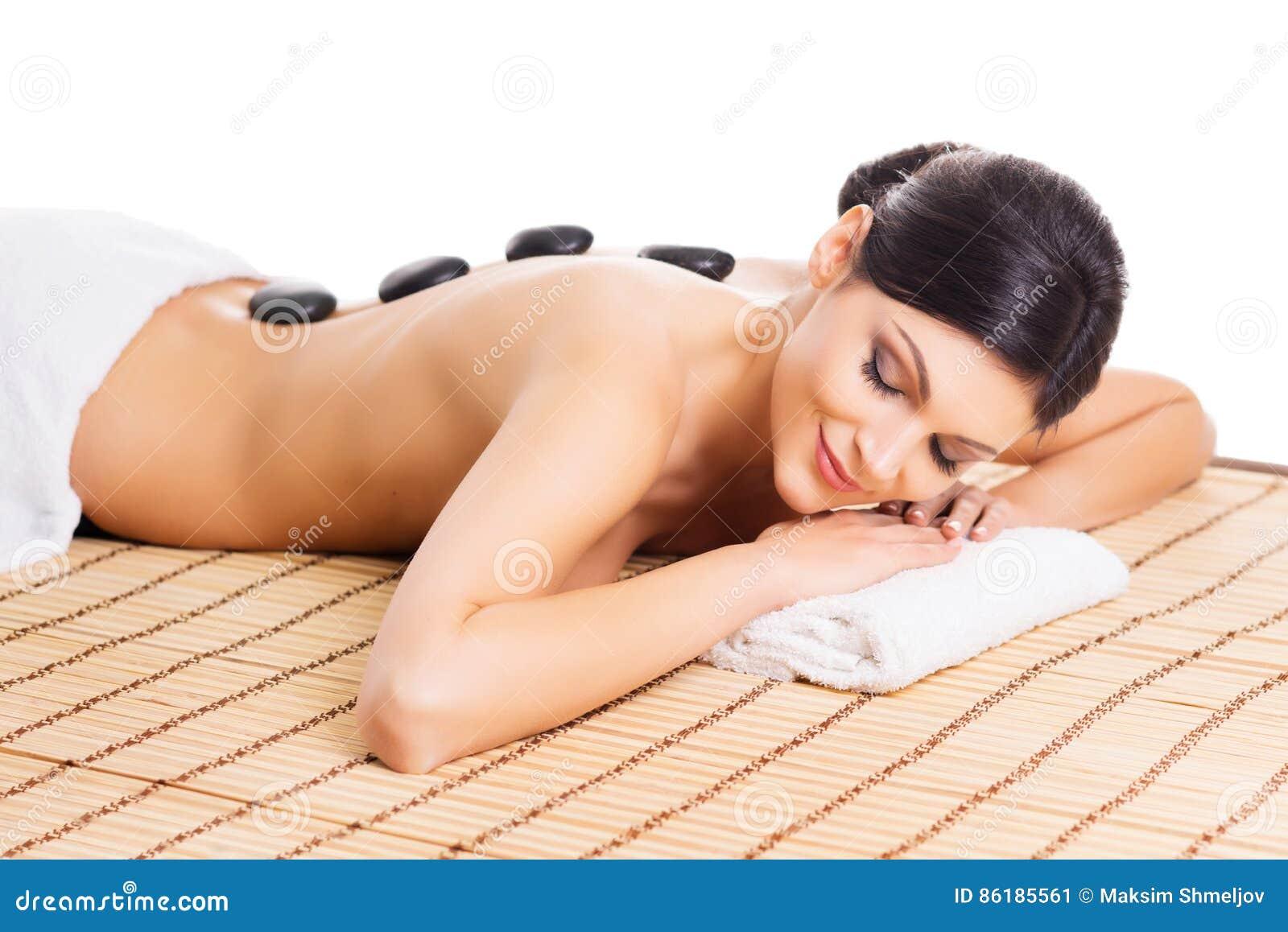 La mujer hermosa, joven y sana en la estera de bambú en salón del balneario está teniendo masaje de piedra caliente