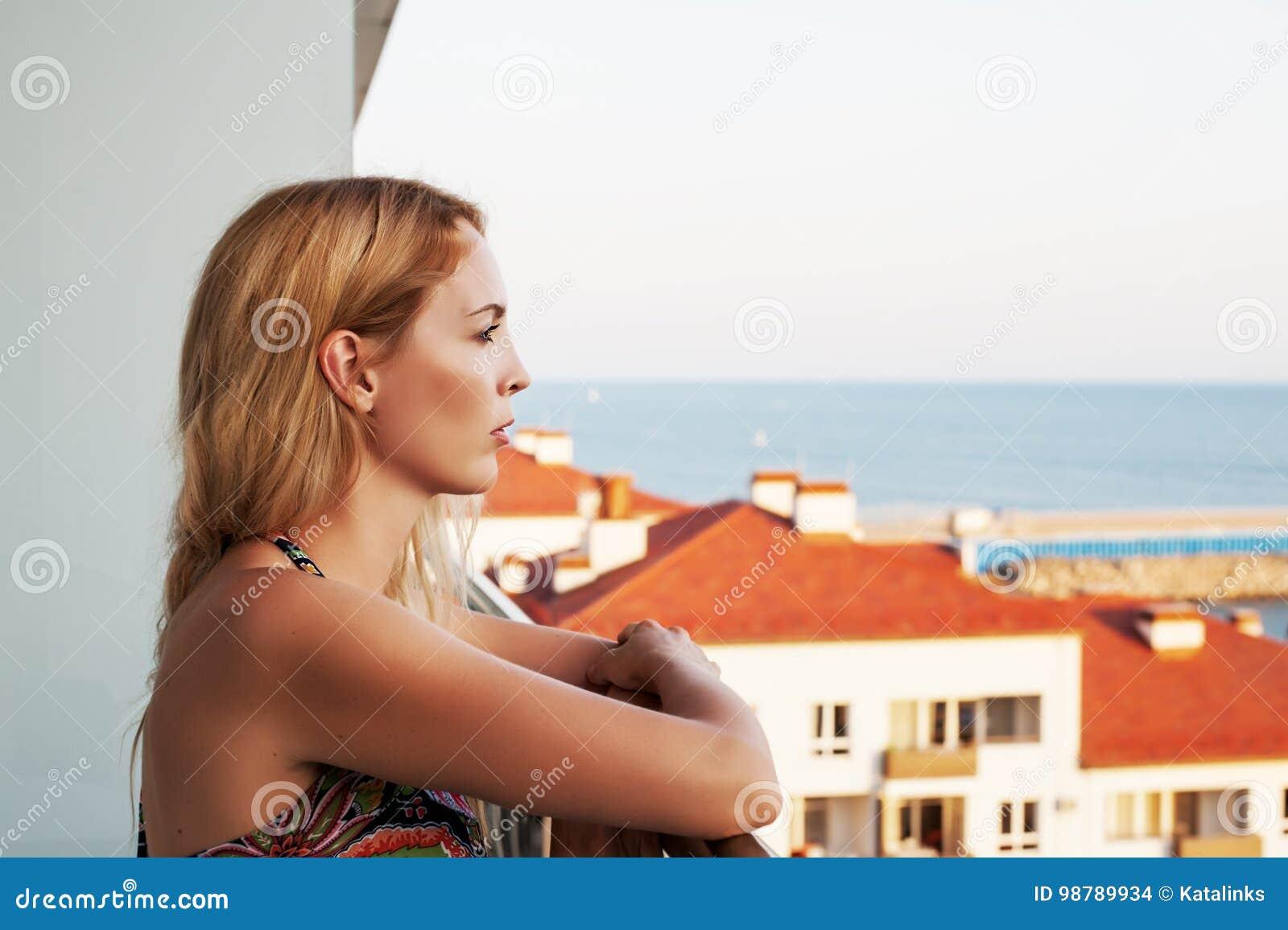 La mujer hermosa mira el mar del balkon del ` s del edificio