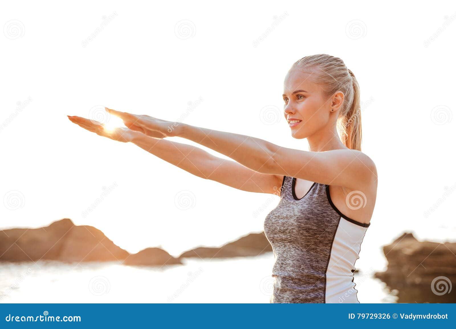 La mujer hermosa que estira las manos ejercita durante yoga en la playa