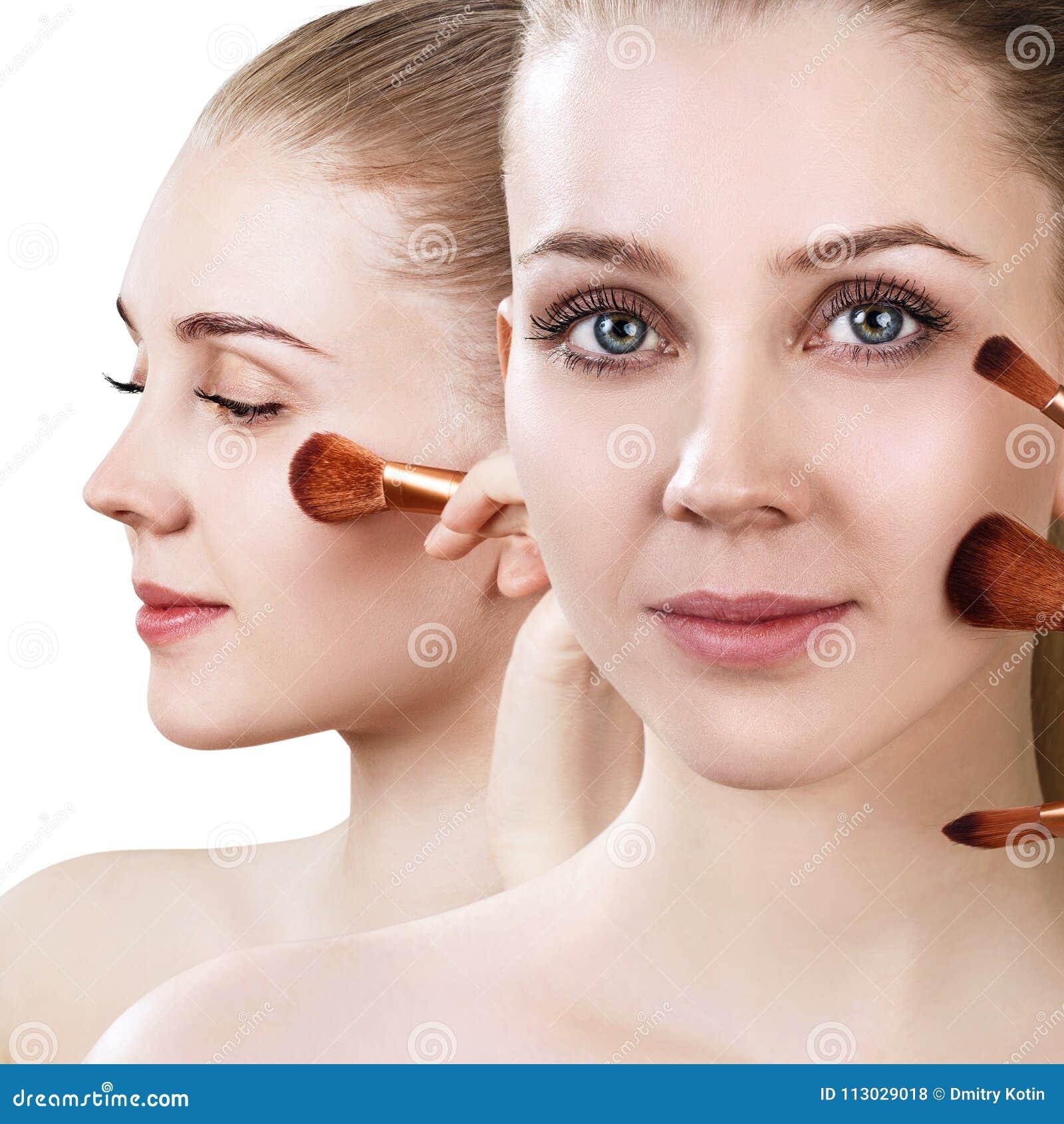 La mujer hermosa sostiene cepillos del maquillaje cerca de cara