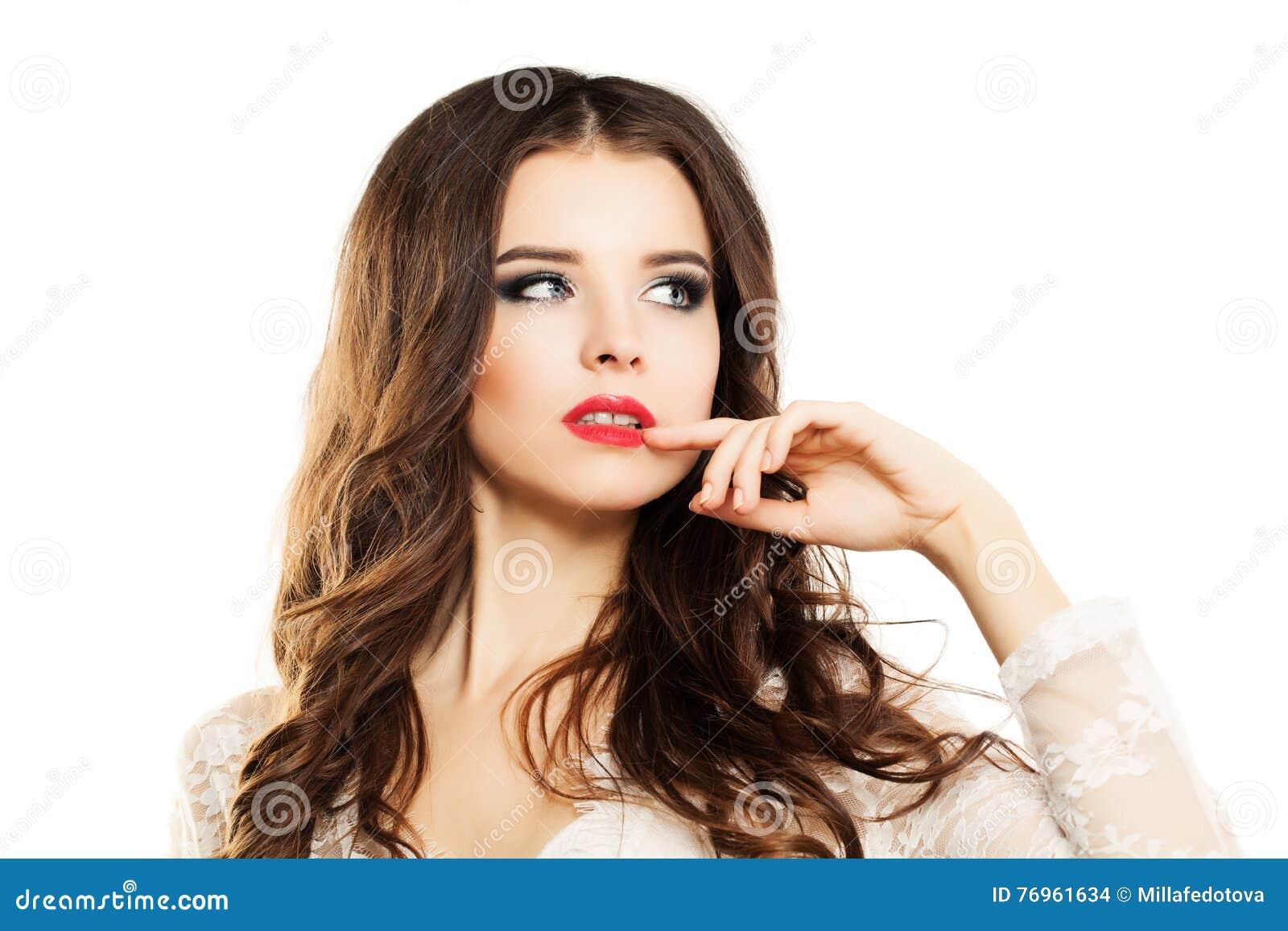 La mujer hermosa toca su mano en sus labios