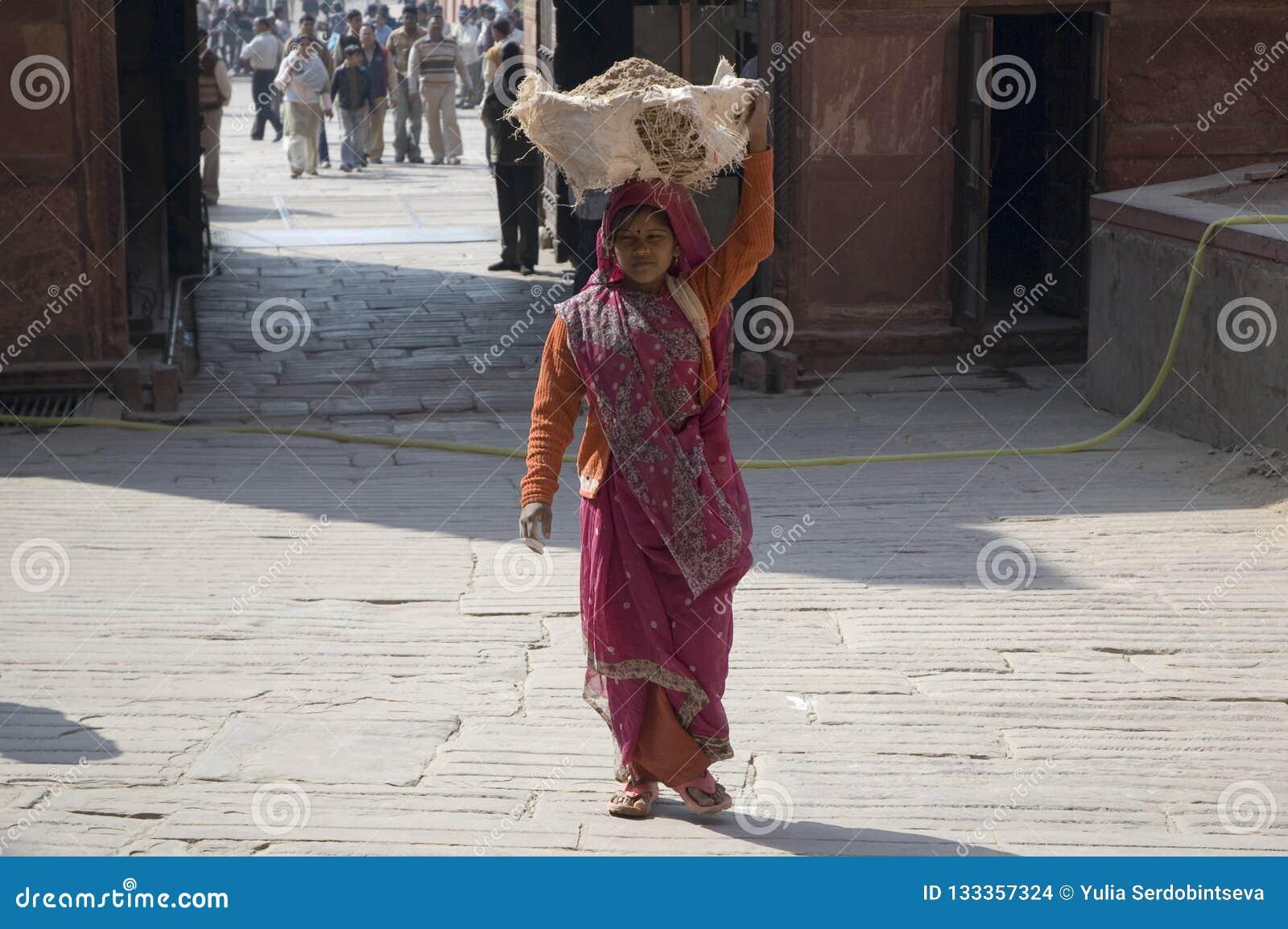 La mujer india lleva la arena en su cabeza Mujer india La India, nueva Delhi 31 de enero de 2009
