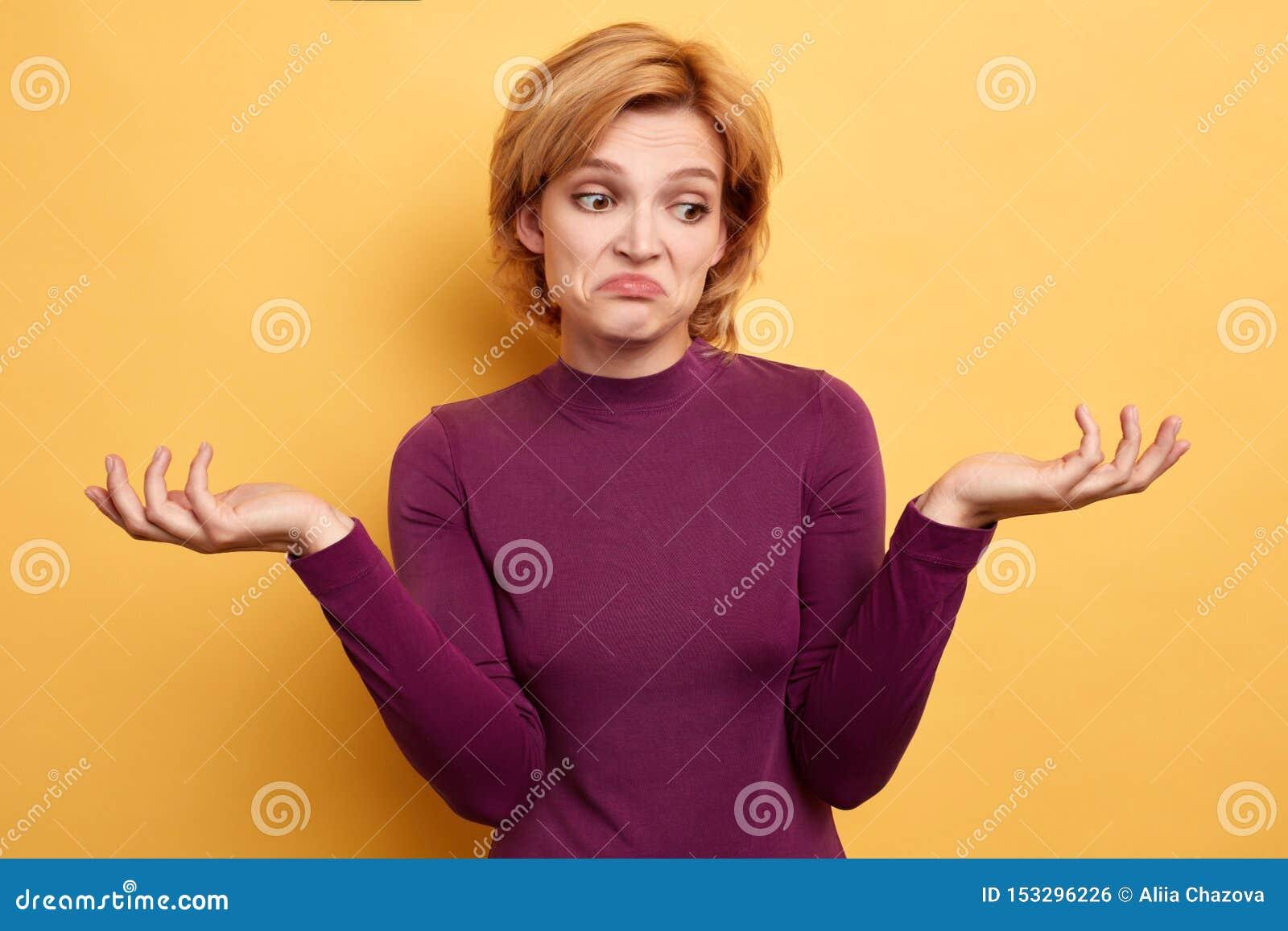 La mujer infeliz triste con las manos aumentadas no puede encontrar la solución del problema