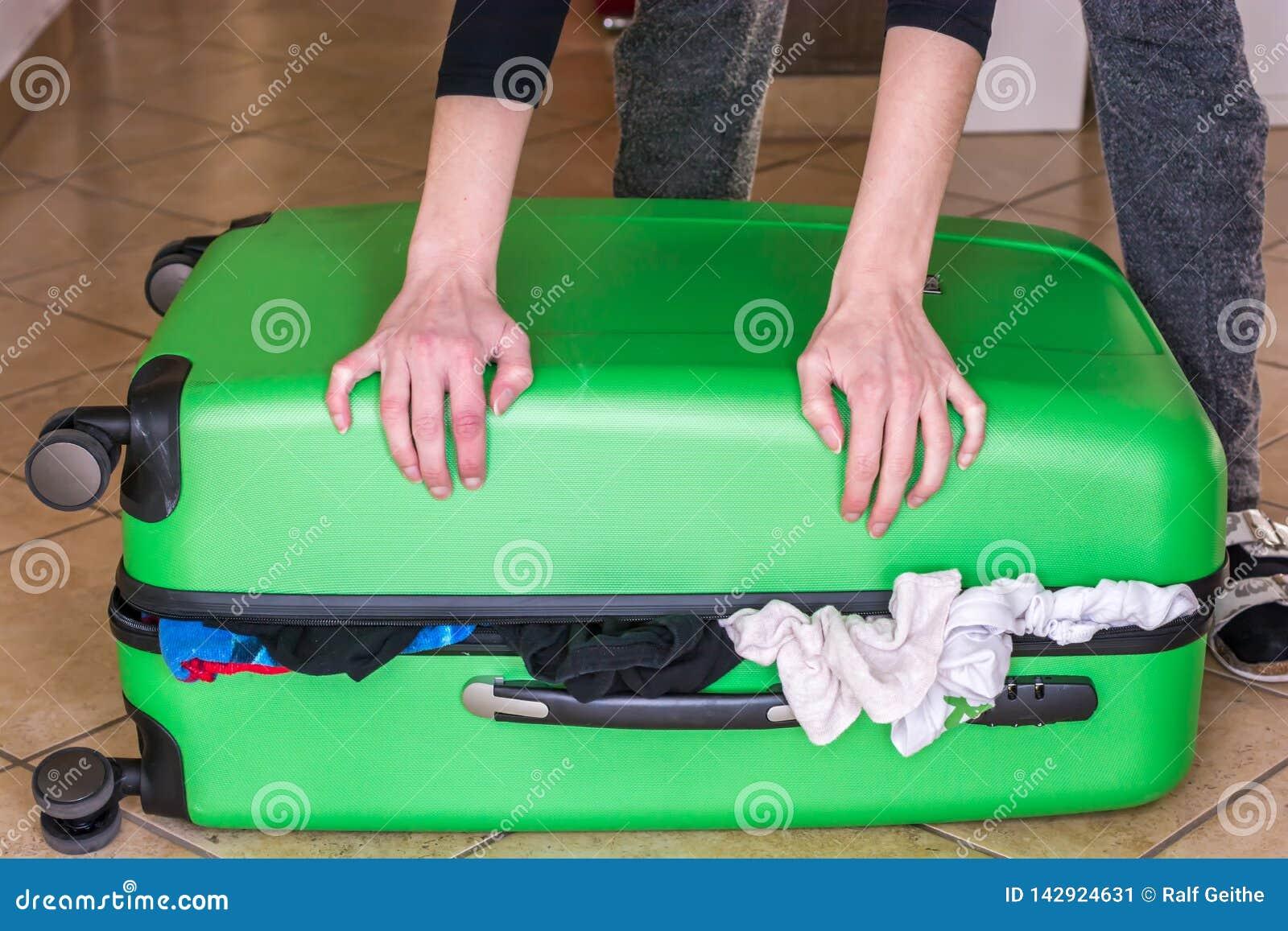 La mujer intenta cerrar la maleta sobrellenada