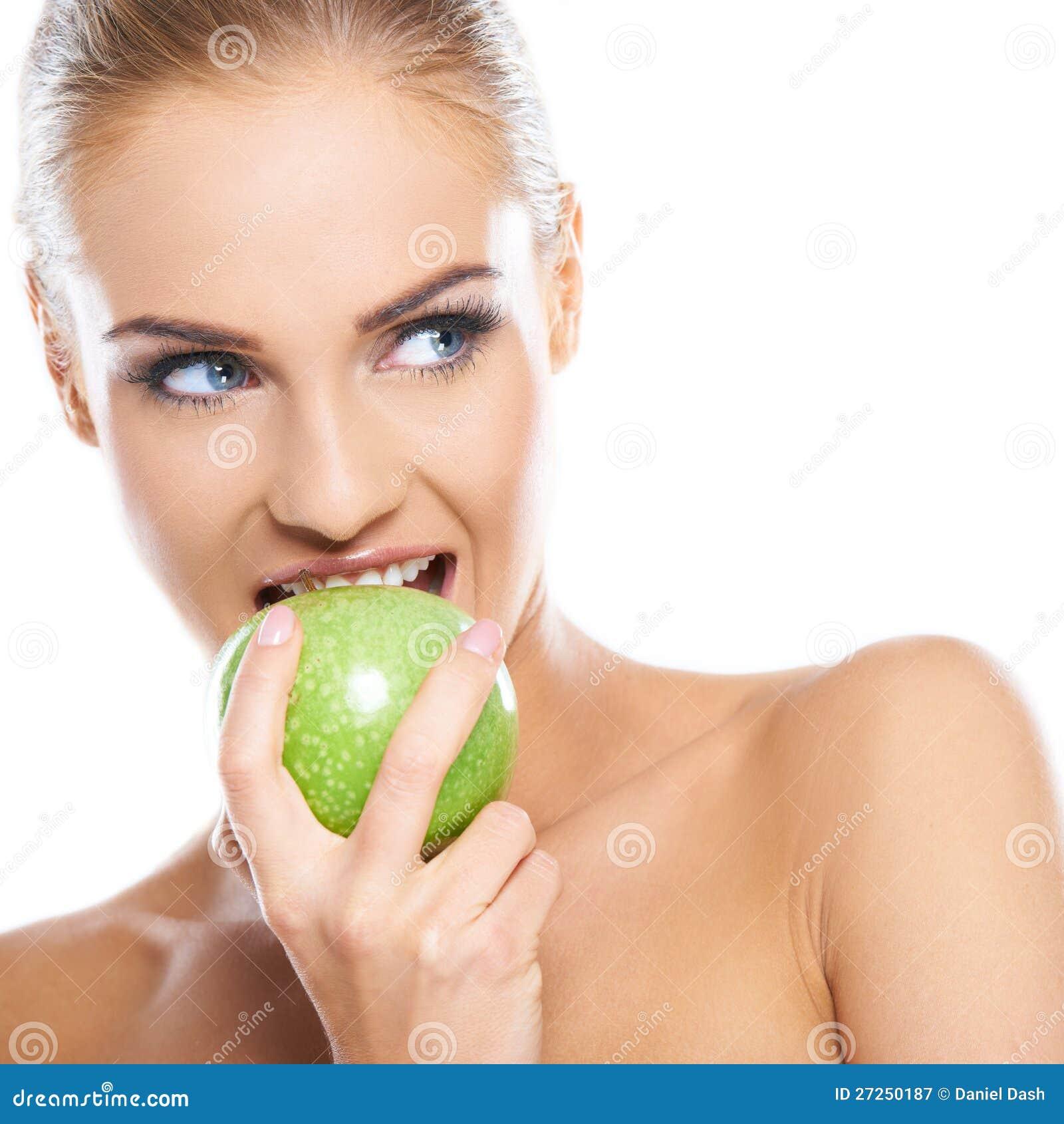 La mujer intenta morder una manzana verde fresca