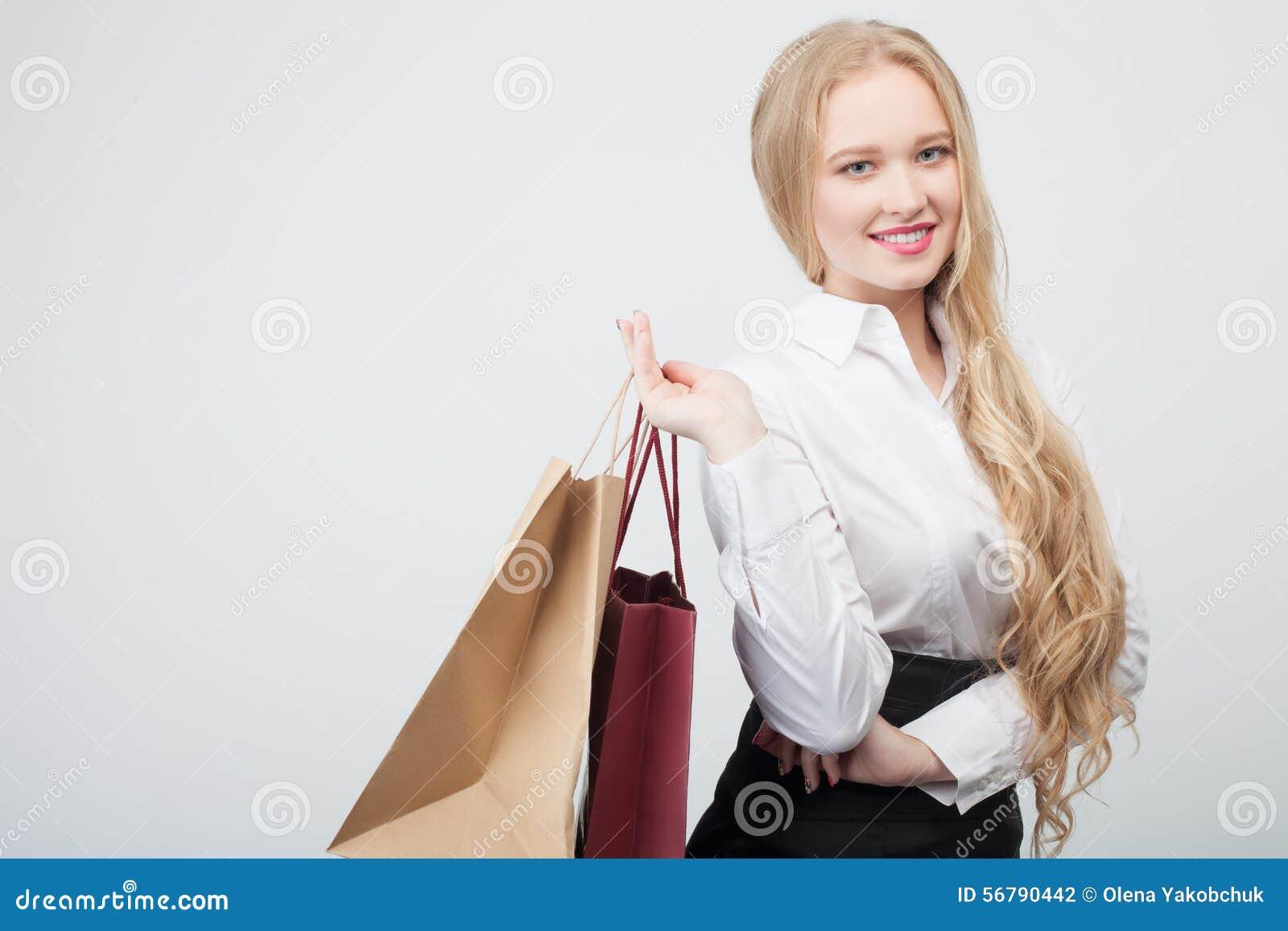 b3d88e21b3 La muchacha rubia atractiva es envío que va Ella está mostrando los  paquetes grandes La señora está mirando la cámara con felicidad y la  sonrisa Aislado en ...