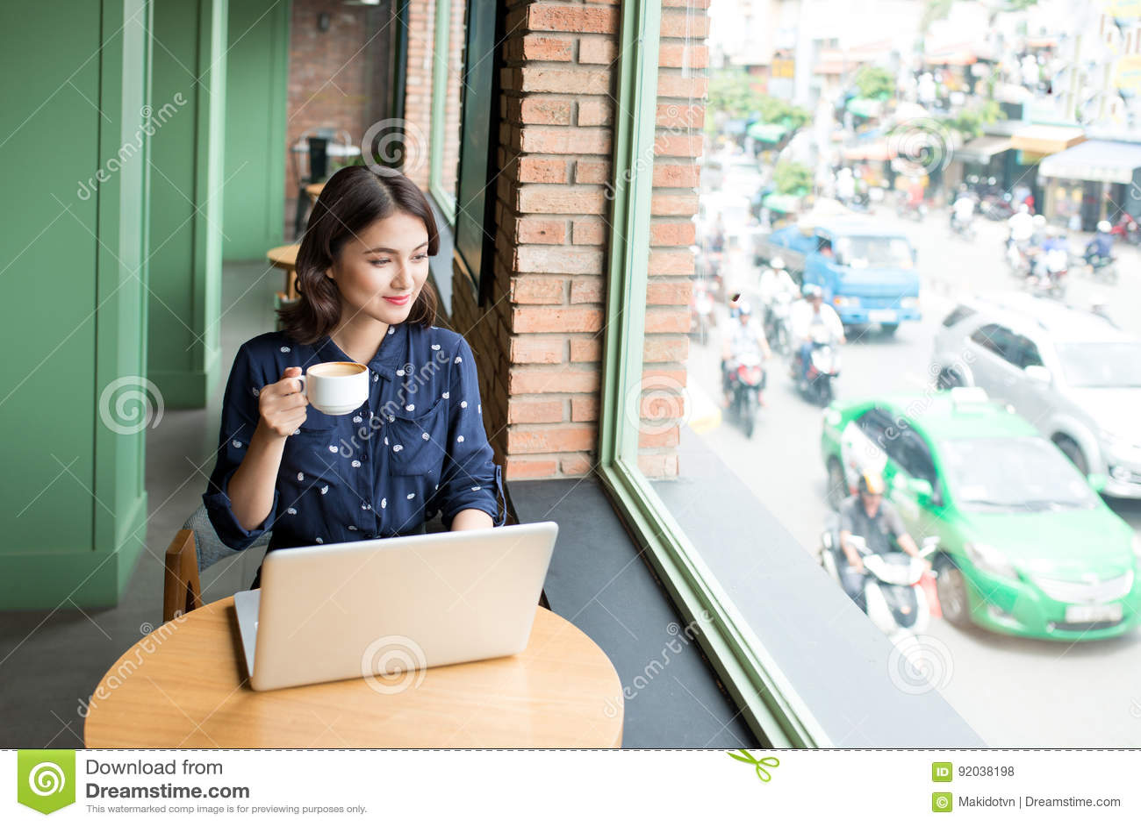 La mujer joven asiática linda hermosa en el café, goza el beber del cof
