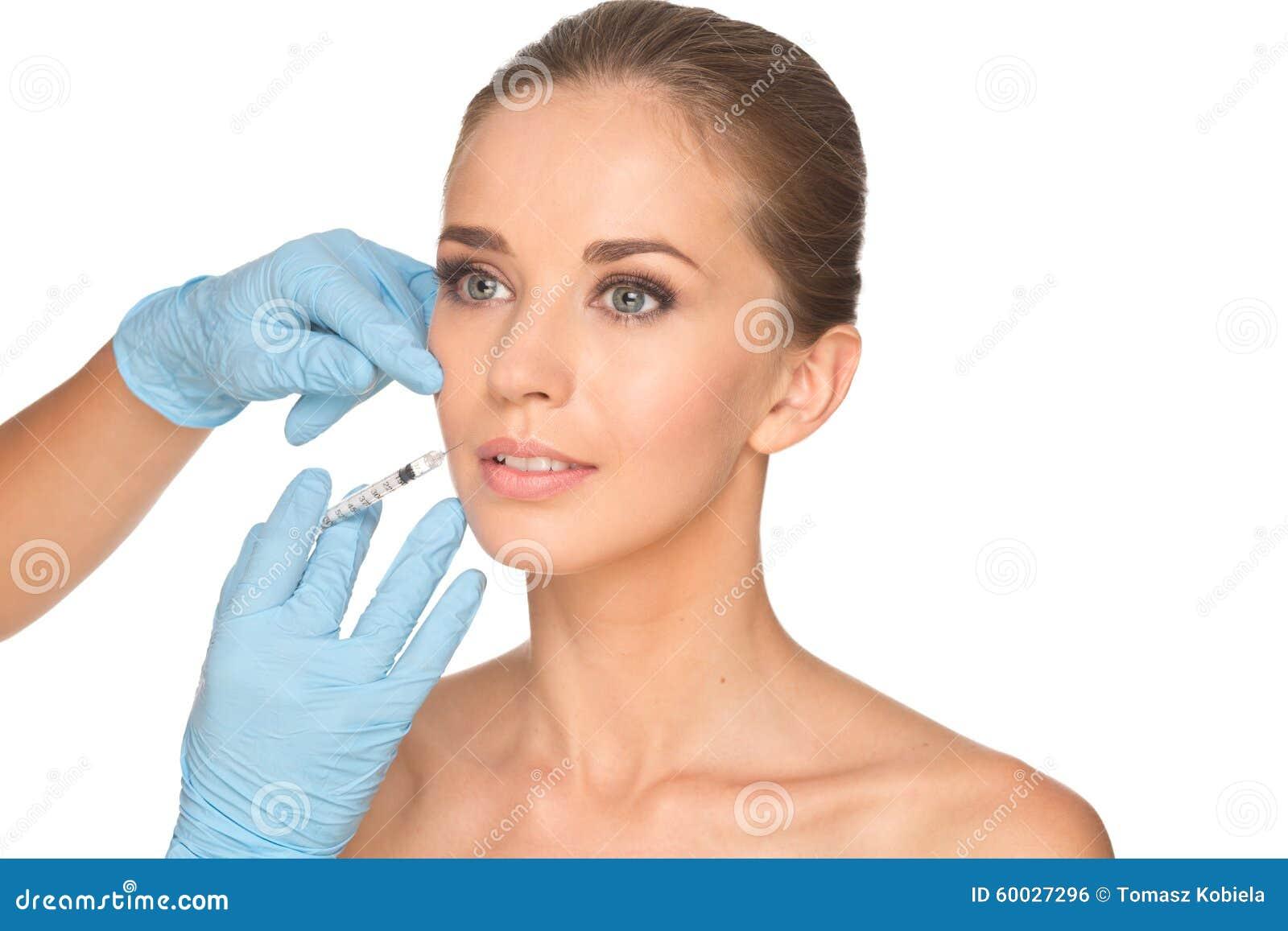 La mujer joven atractiva consigue la inyección cosmética del botox