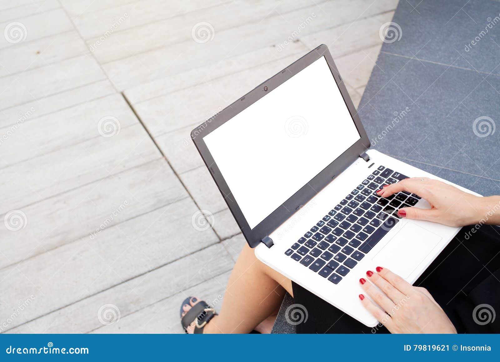 La mujer joven atractiva está trabajando en el ordenador portátil