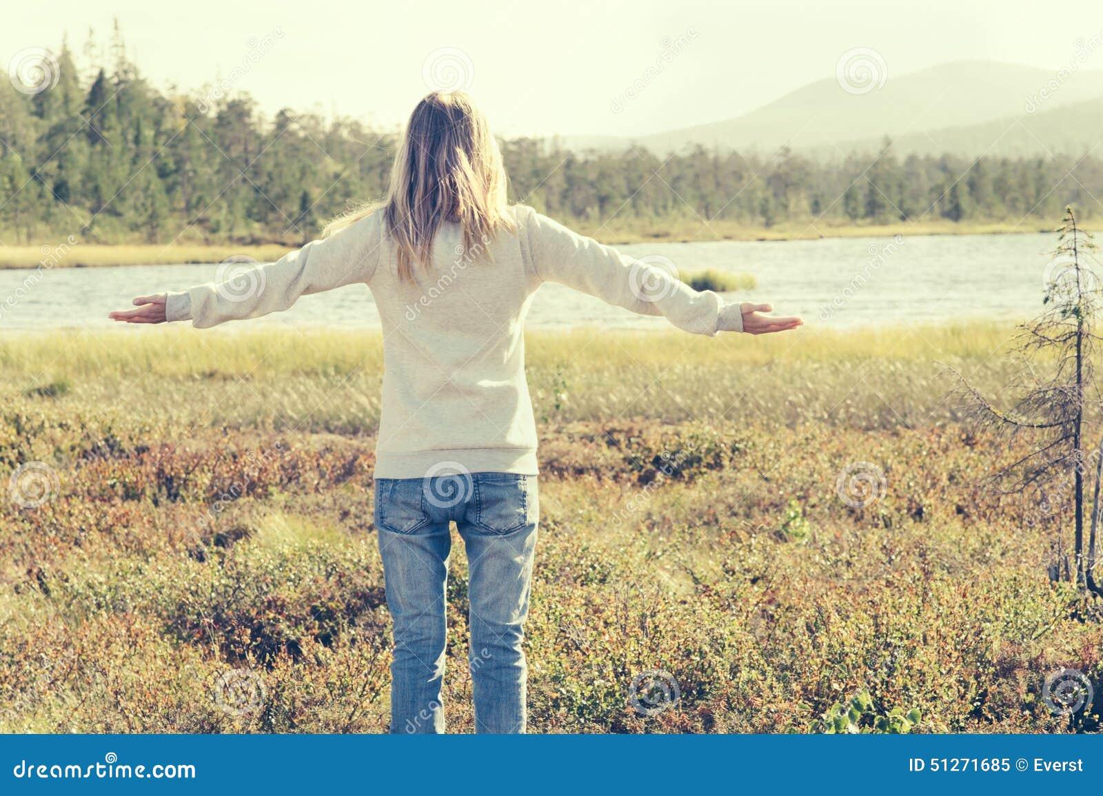 La mujer joven aumentó las manos que colocaban viaje al aire libre solamente que caminaba