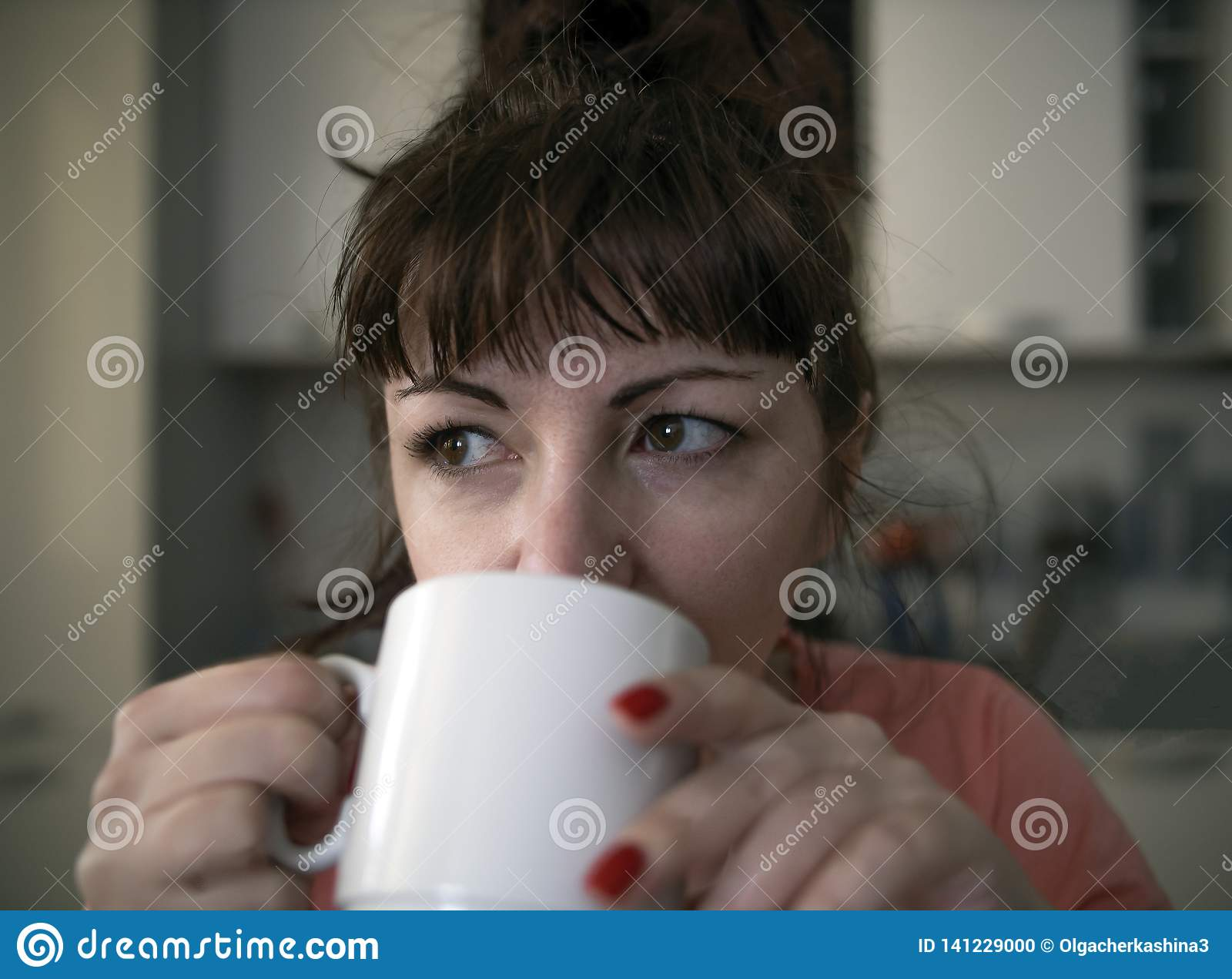 La mujer joven bebe el café por la mañana en la cocina, ojos cansados con las venas rojas, primer