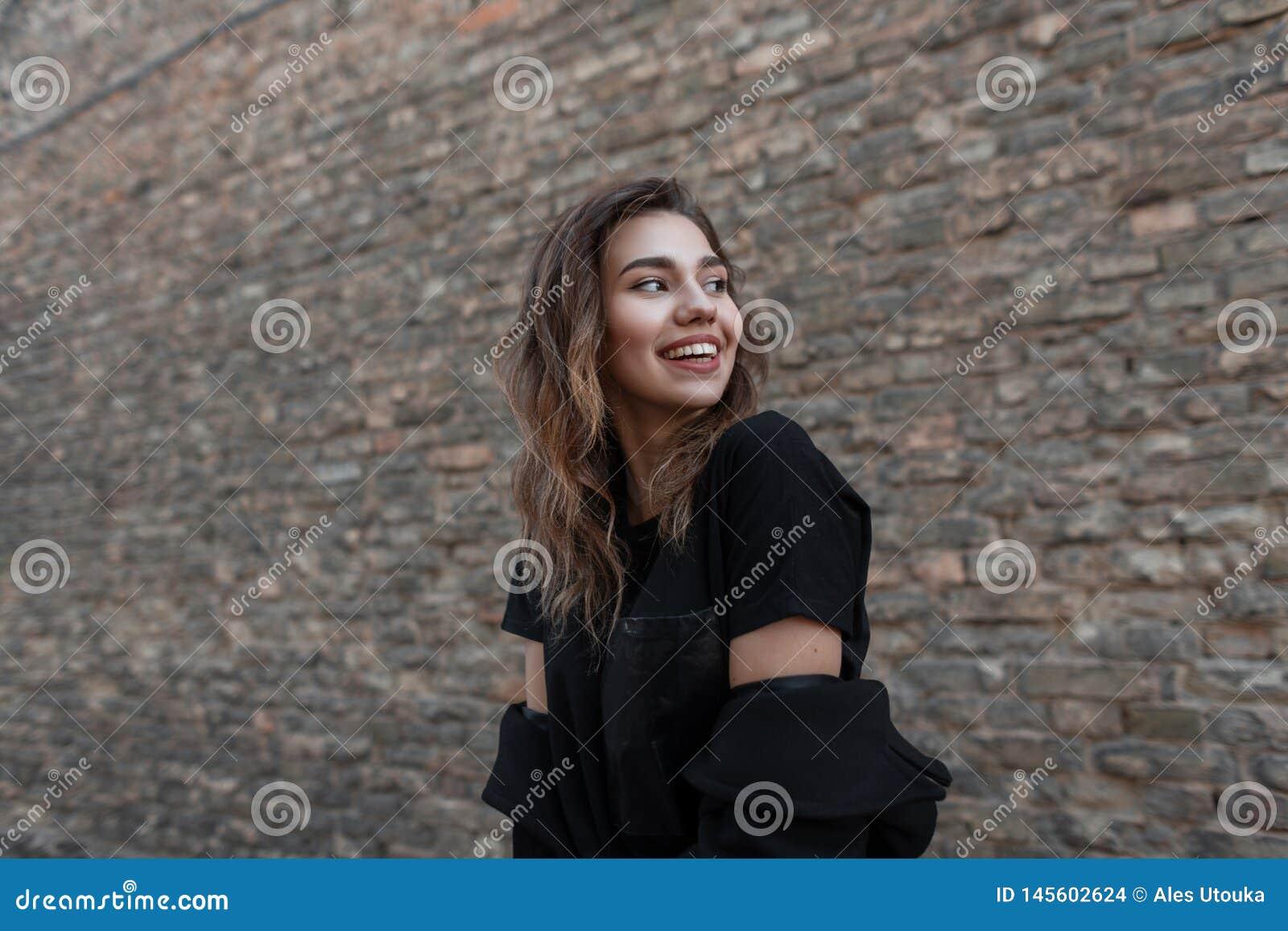 La mujer joven bonita alegre en una capa de moda en una camiseta elegante negra con una sonrisa hermosa positiva se está colocand