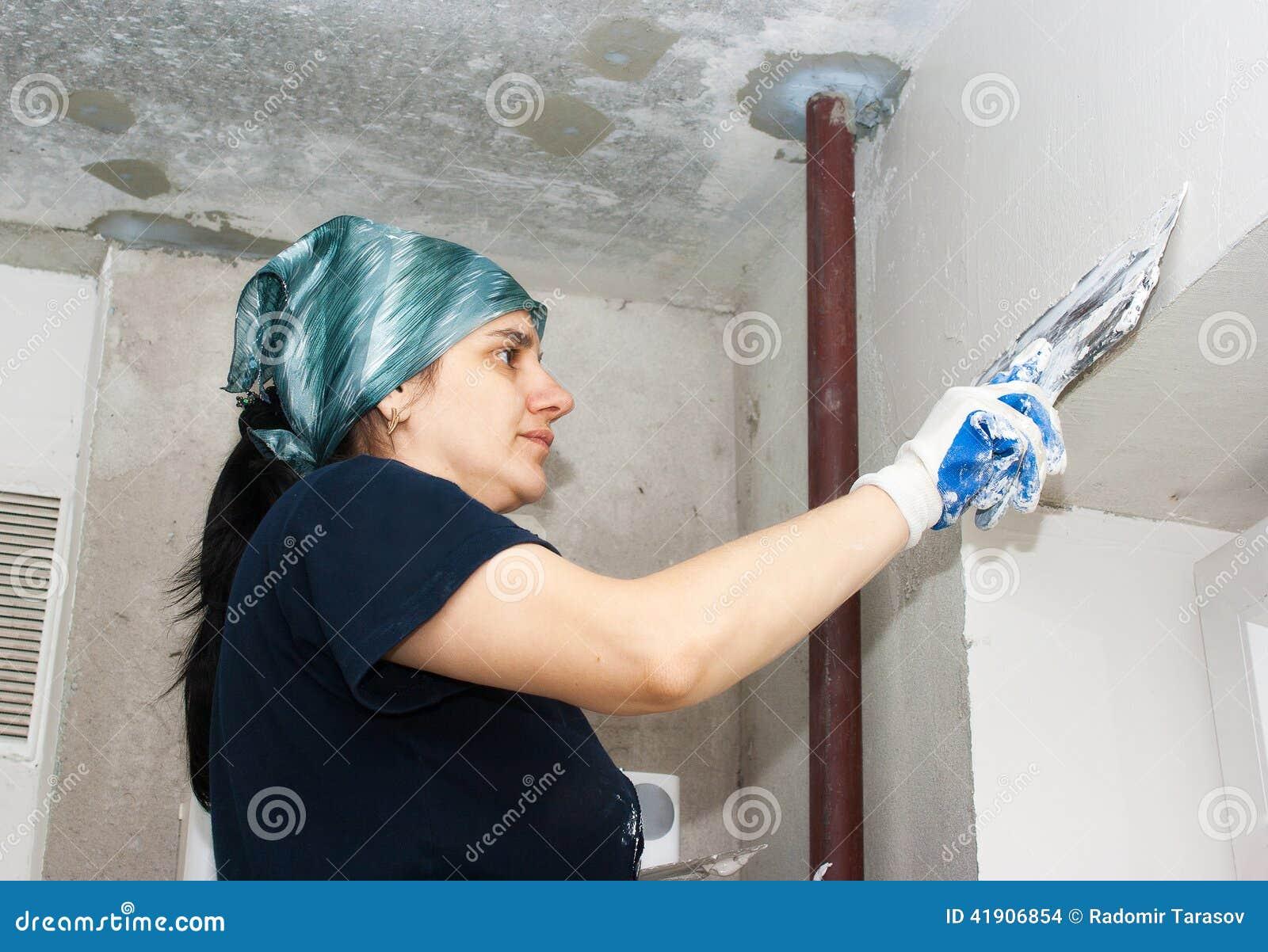 La mujer joven consigue la pared del yeso
