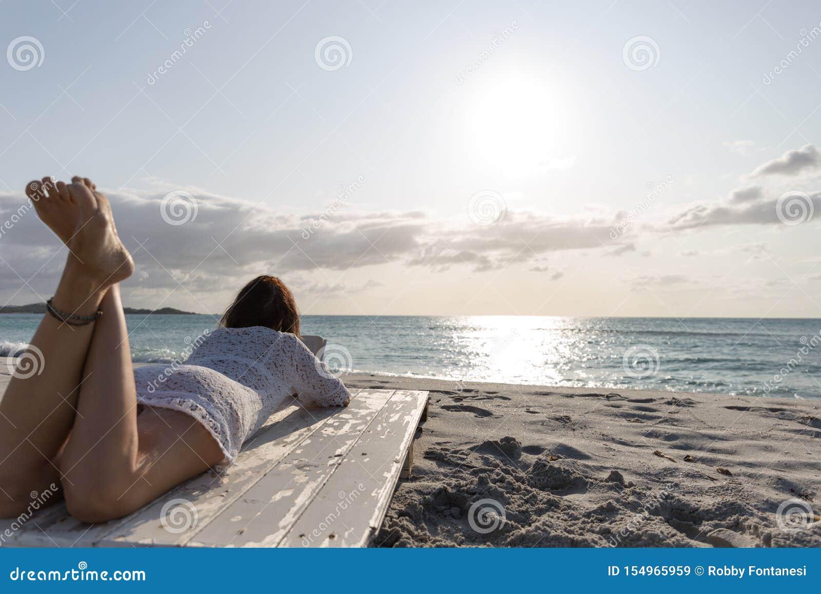 La mujer joven de detrás la mentira por las miradas del mar en el horizonte en el amanecer en el viento, vestido en un vestido y